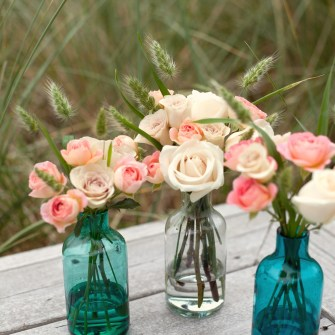 local roses and grass in simple beach bottles