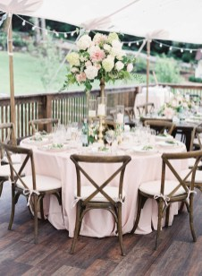 Wedding reception table with tall flower centerpiece on gold stand with gold candle holders around the base, ivory table linen, Vineyard chairs