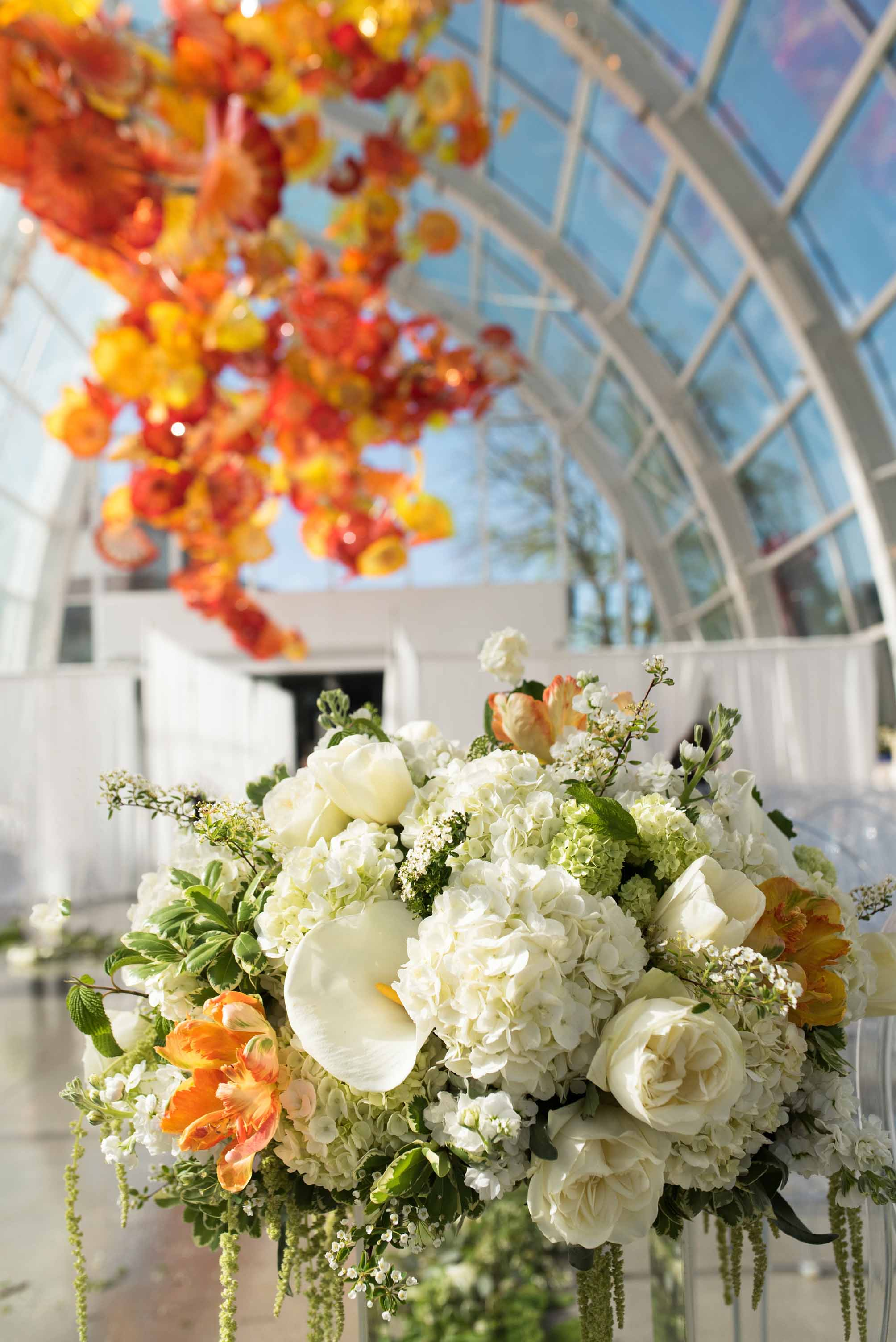 Large white and orange flower design with white calla lilies, white hydrangea, white roses, orange parrot tulips, and spring greenery inside Chihuly glass house in Seattle