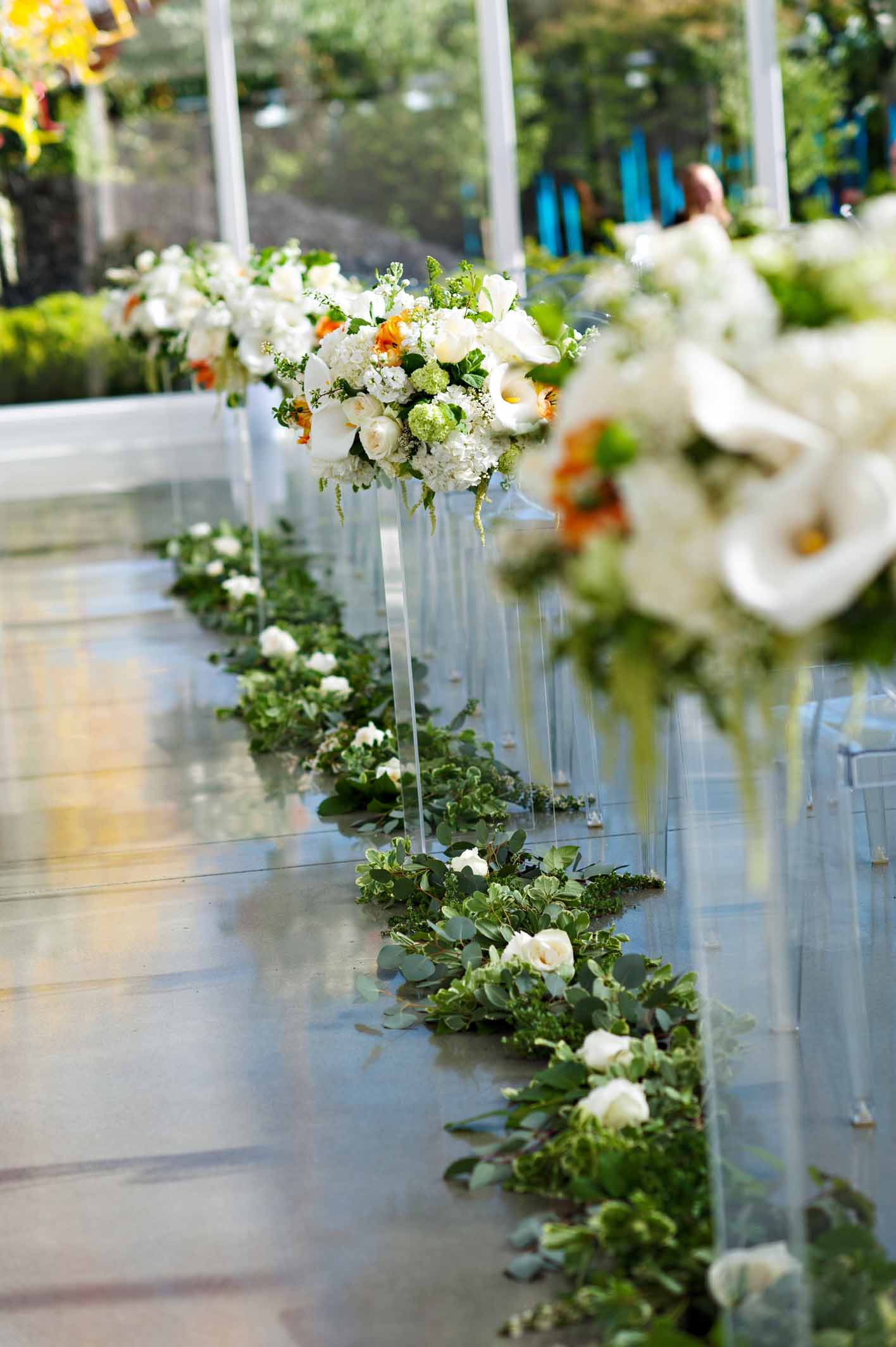 Wedding ceremony aisle lined with large white flower arrangements propped onto clear lucite pedestals, with greenery garland on the floor - Chihuly Wedding Seattle - Flora Nova Design Seattle