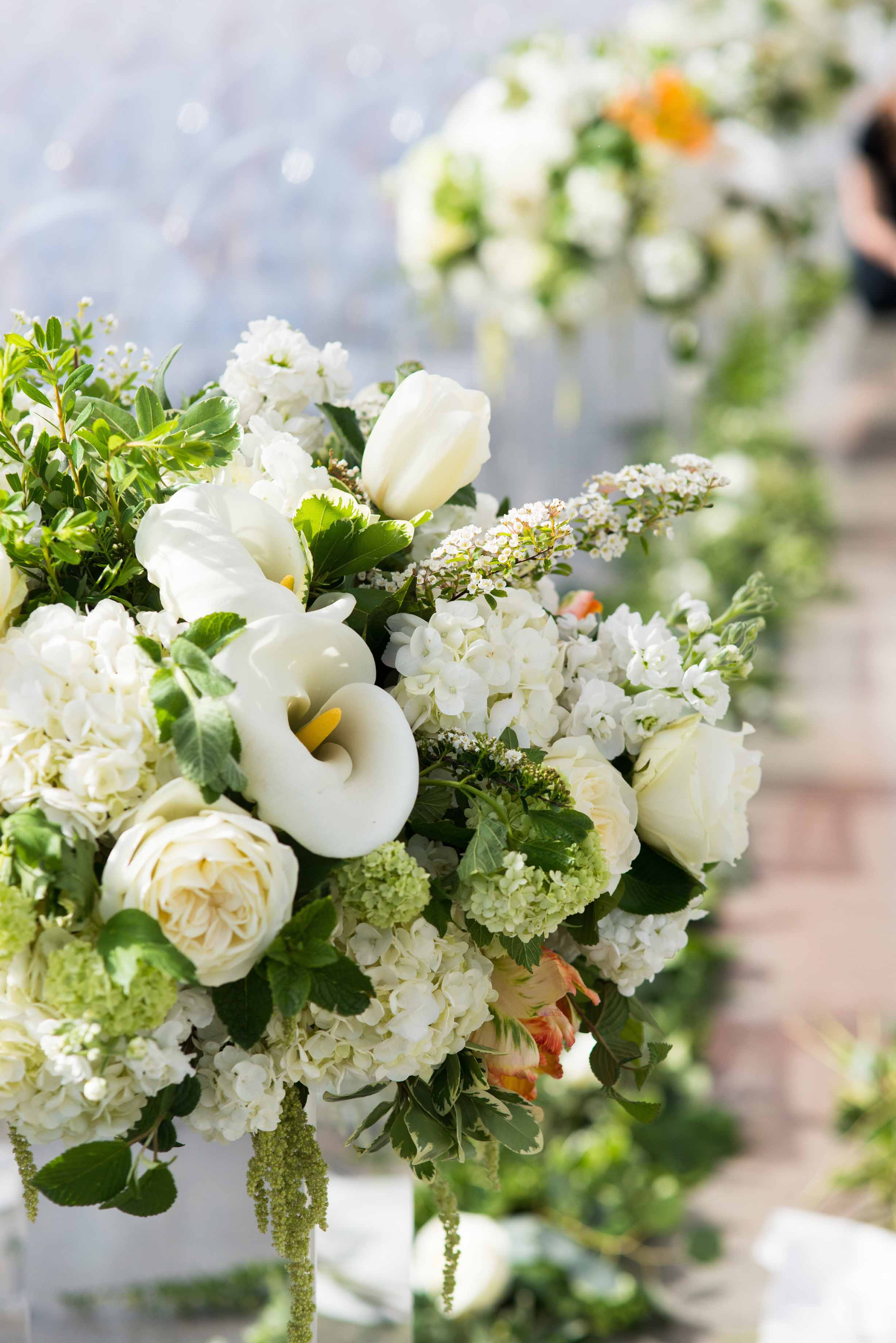 Beautiful white and orange floral design with large white calla lilies, white roses, viburnum, blooming spirea, and parrot tulips