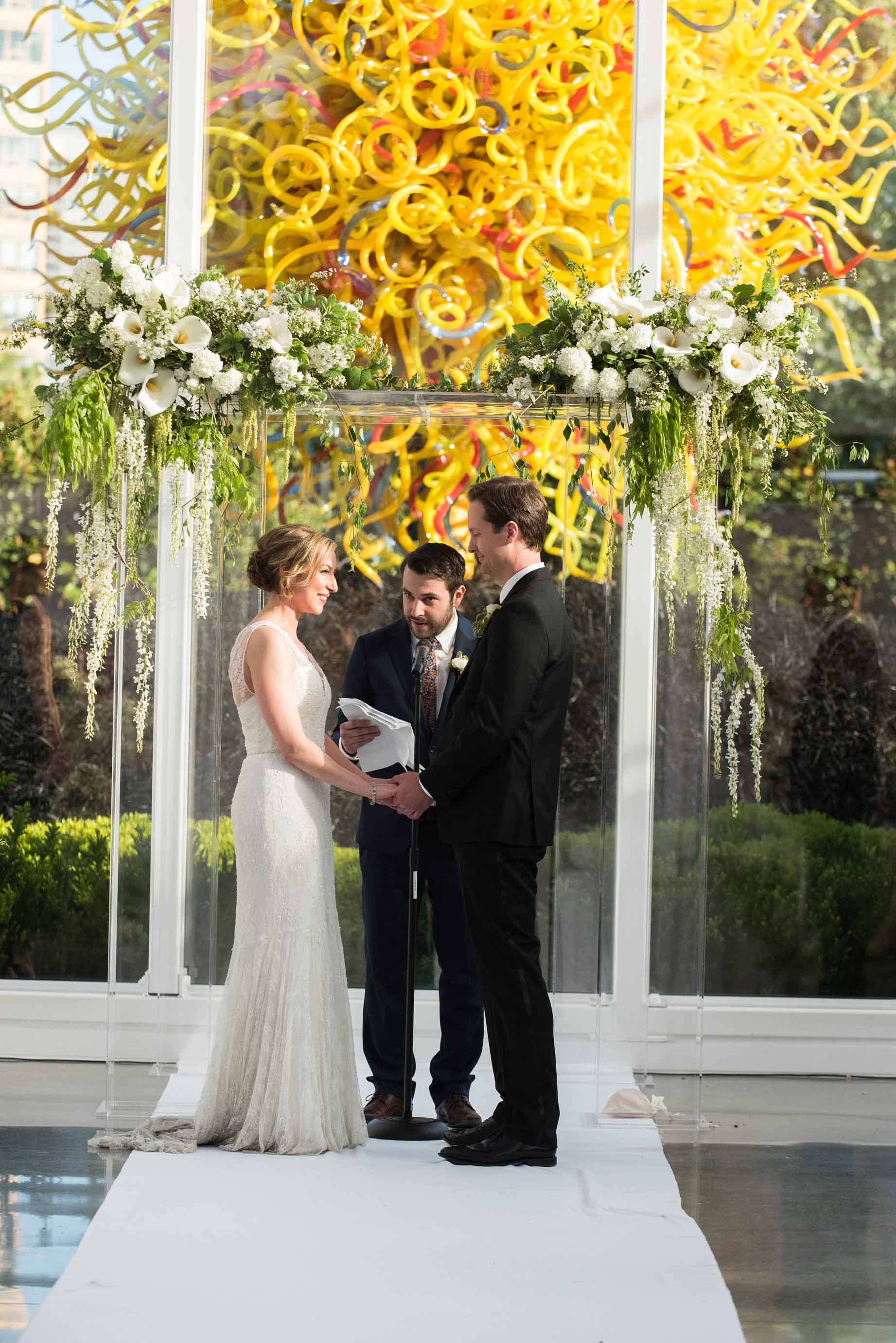 Bride and groom at their Chihuly wedding standing in front of lucite chuppah decorated with greenery and white flowers