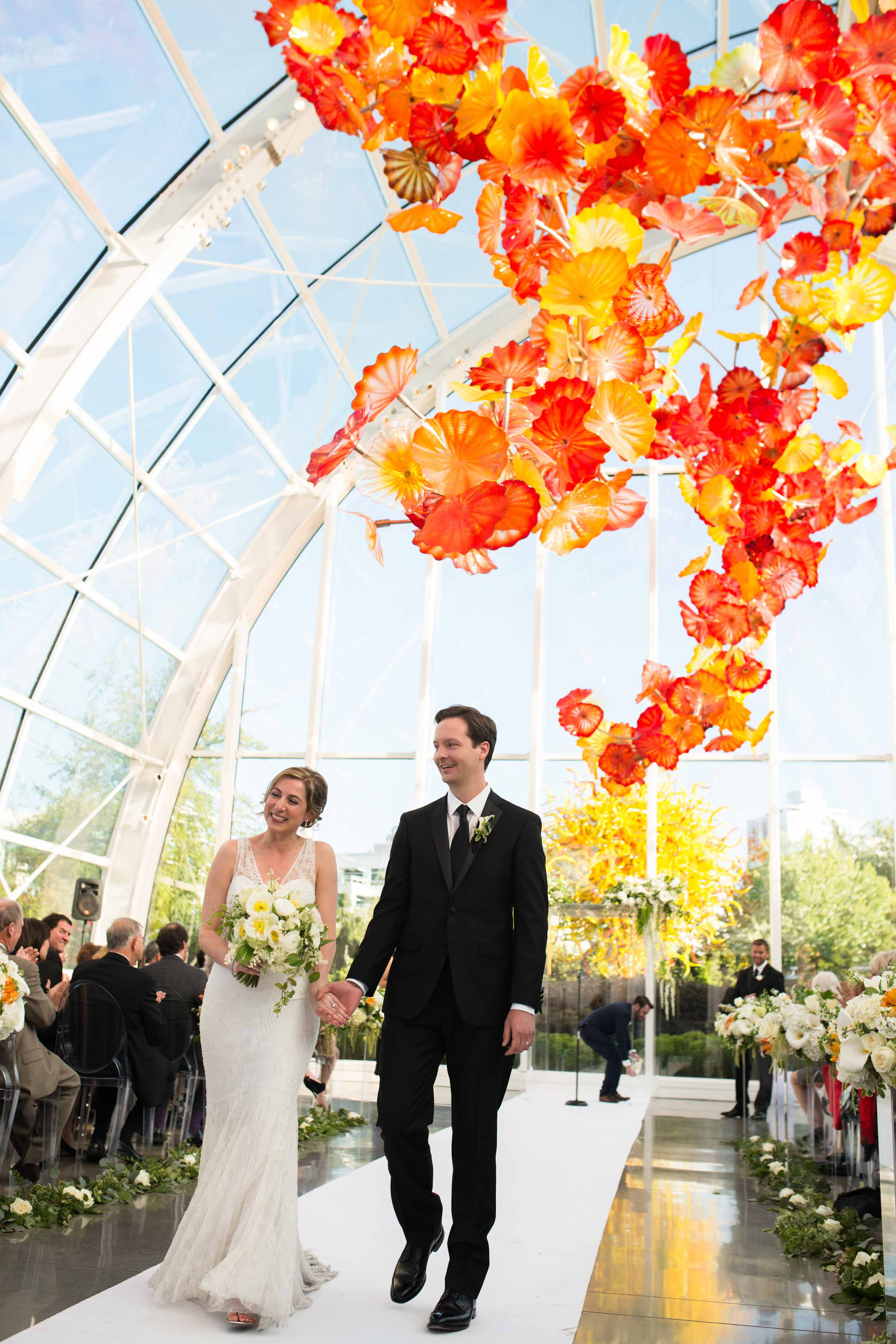 Bride and Groom walking down the aisle at their Chihuly Garden and Glass Wedding in Seattle - by Flora Nova Design