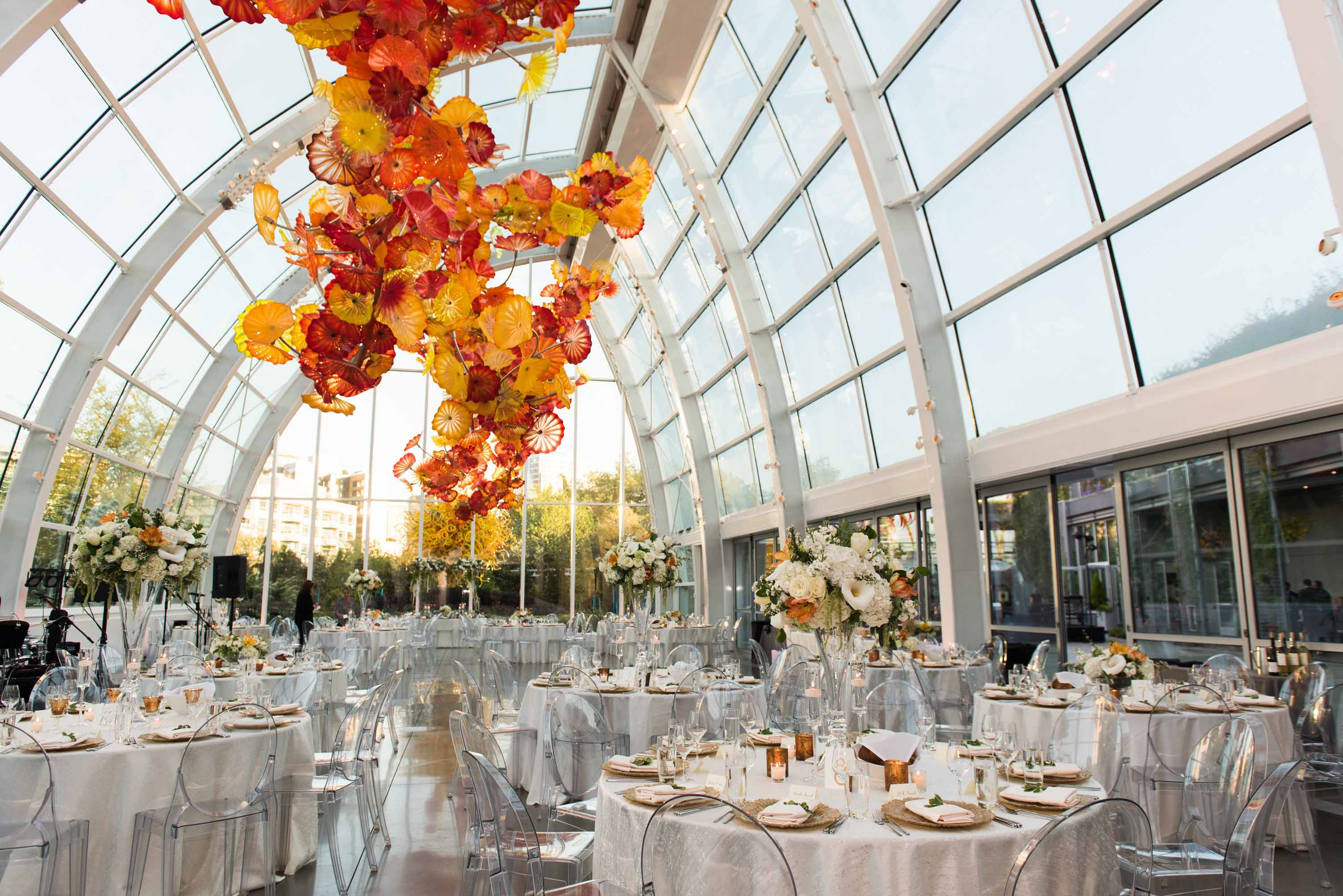 reception at Chihuly Garden and Glass wedding featuring clear ghost chairs, round tables covered in ivory silk, and large flower arrangements in orange and white - Flora Nova Design