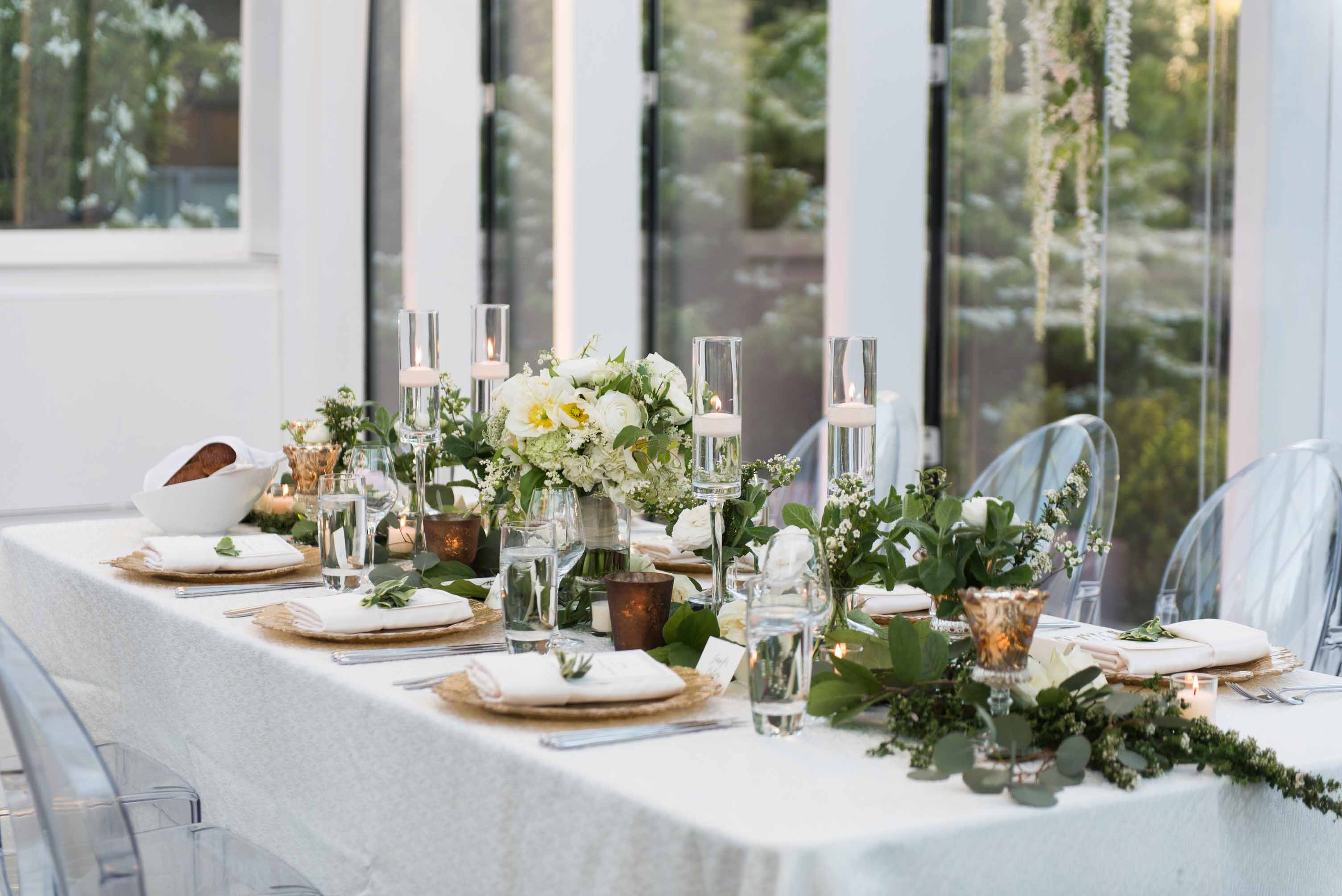 Wedding reception head table lined with greenery garland, spring flowers, gold charger plates, glass hurricane candles, and gold votives