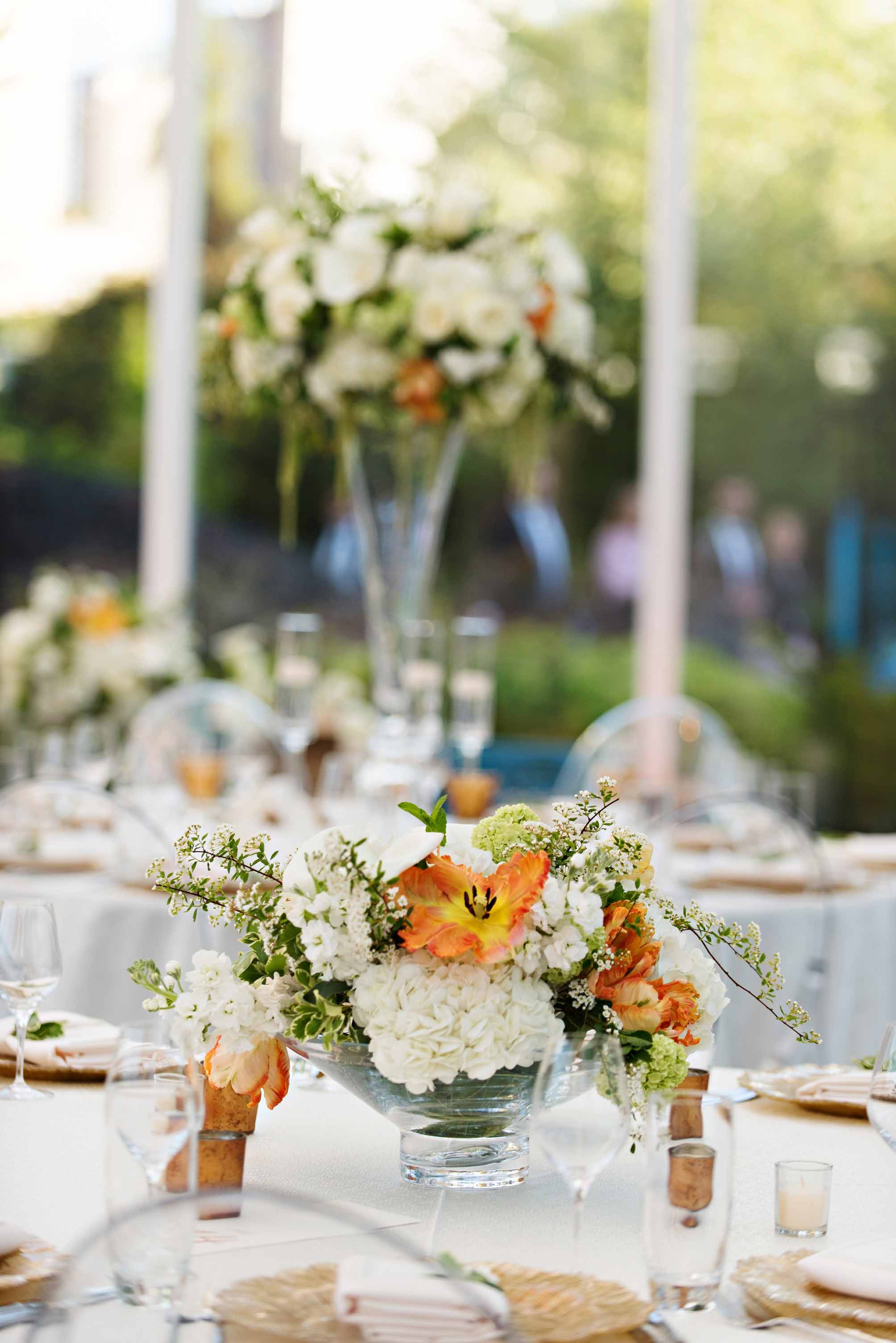 Tall and low centerpieces with white and orange spring flowers on wedding reception tables - by Flora Nova Design