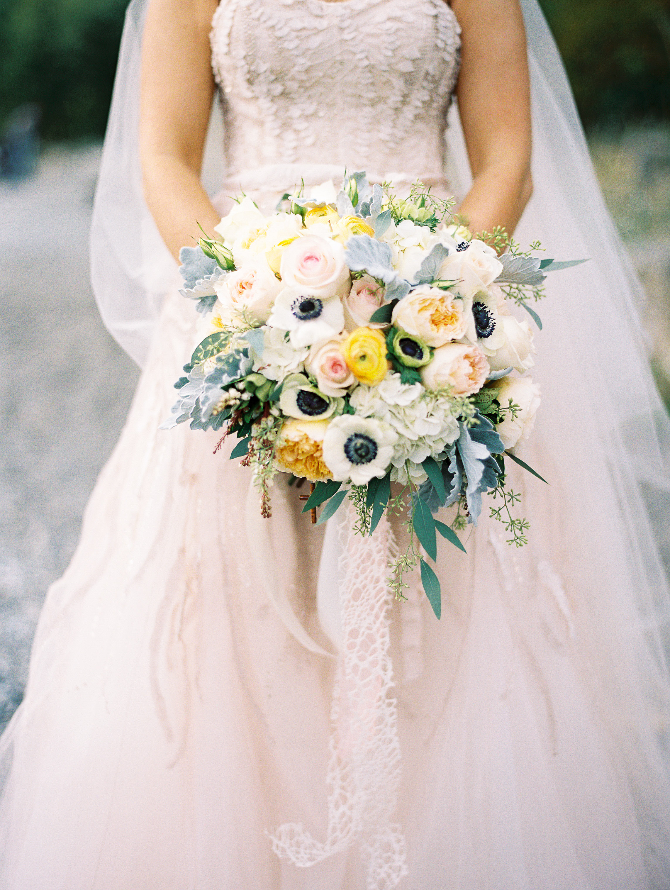 Yellow and ivory bridal bouquet of roses, hydrangea, anemones, ranunculus, with textured greenery - designed By Flora Nova Design
