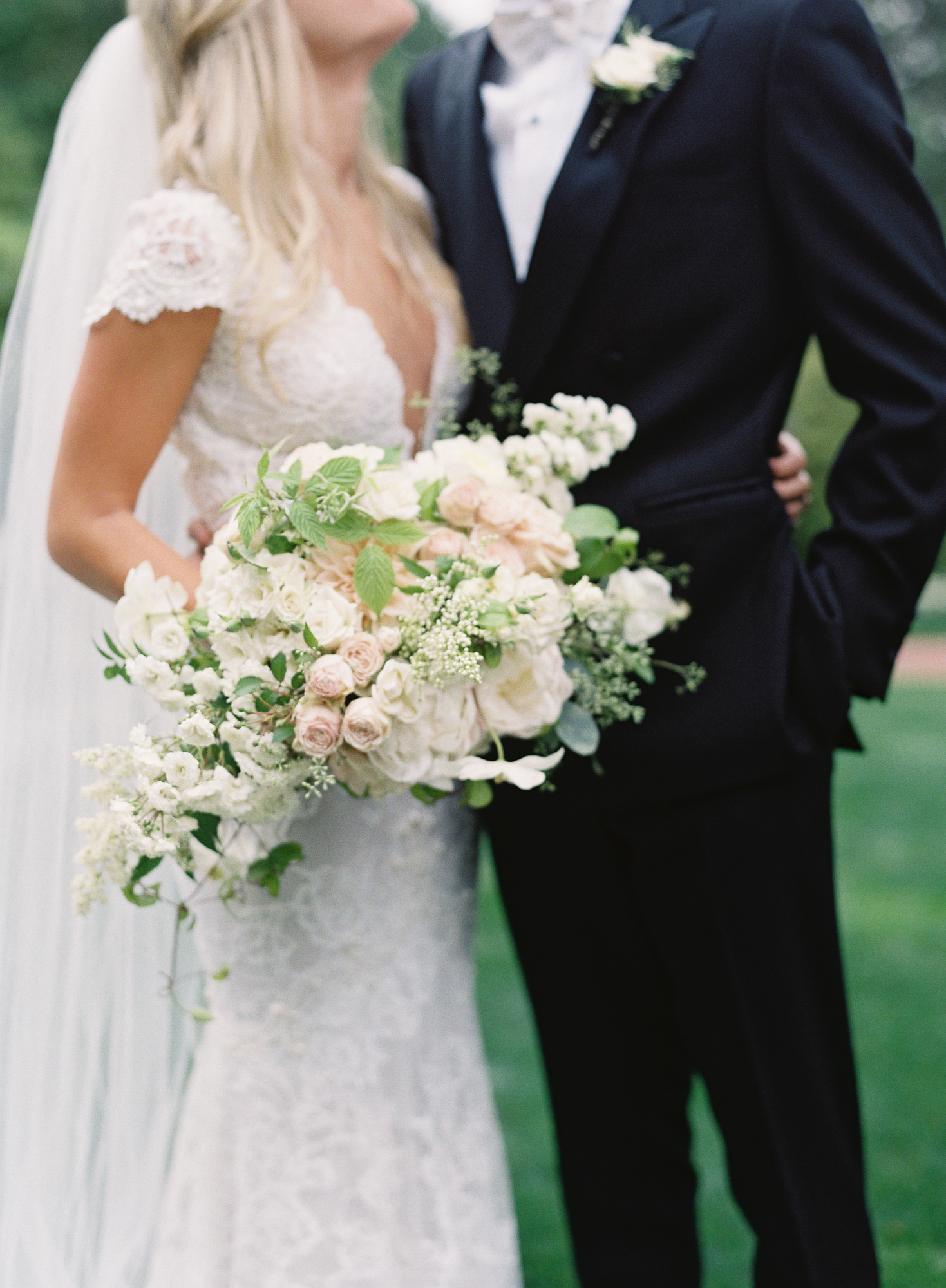 Bridal bouquet in garden style with ivory roses, peonies, and fairy roses, with accents of greenery