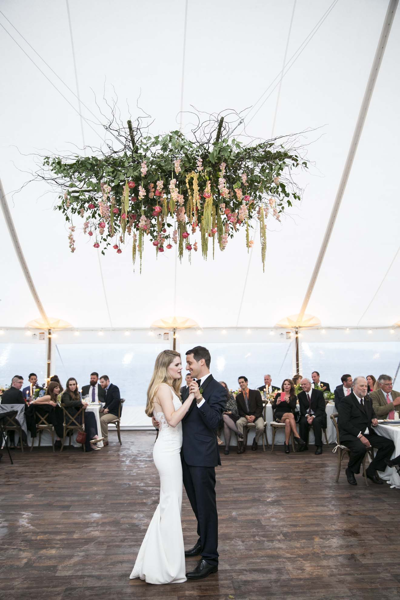 Wedding couple dancing in wedding tent with large floral chandeliers above dance floor - A Pacific Northwest Wedding by Flora Nova Design