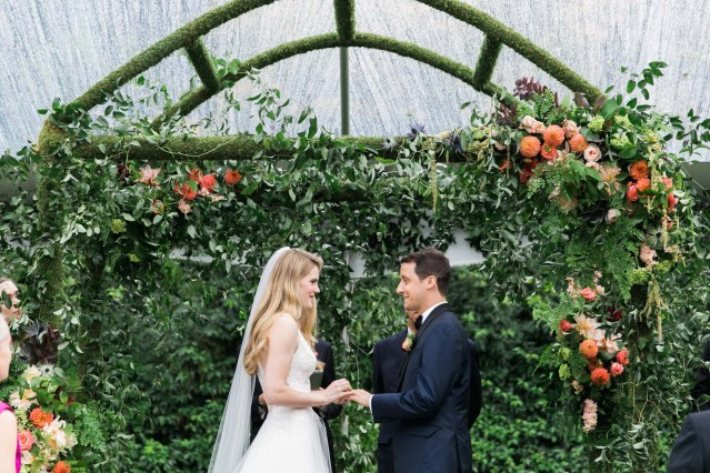 Wedding couple getting married under a custom moss arch covered in greenery vines and orange, peach flowers