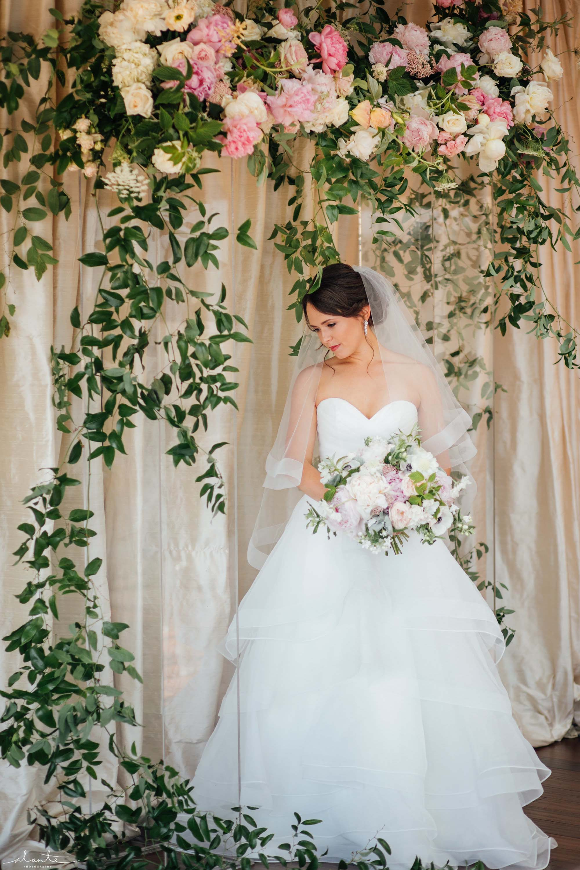 Bride under a lucite wedding arch, Olympic Rooftop Pavilion wedding with pink peonies by Flora Nova Design Seattle