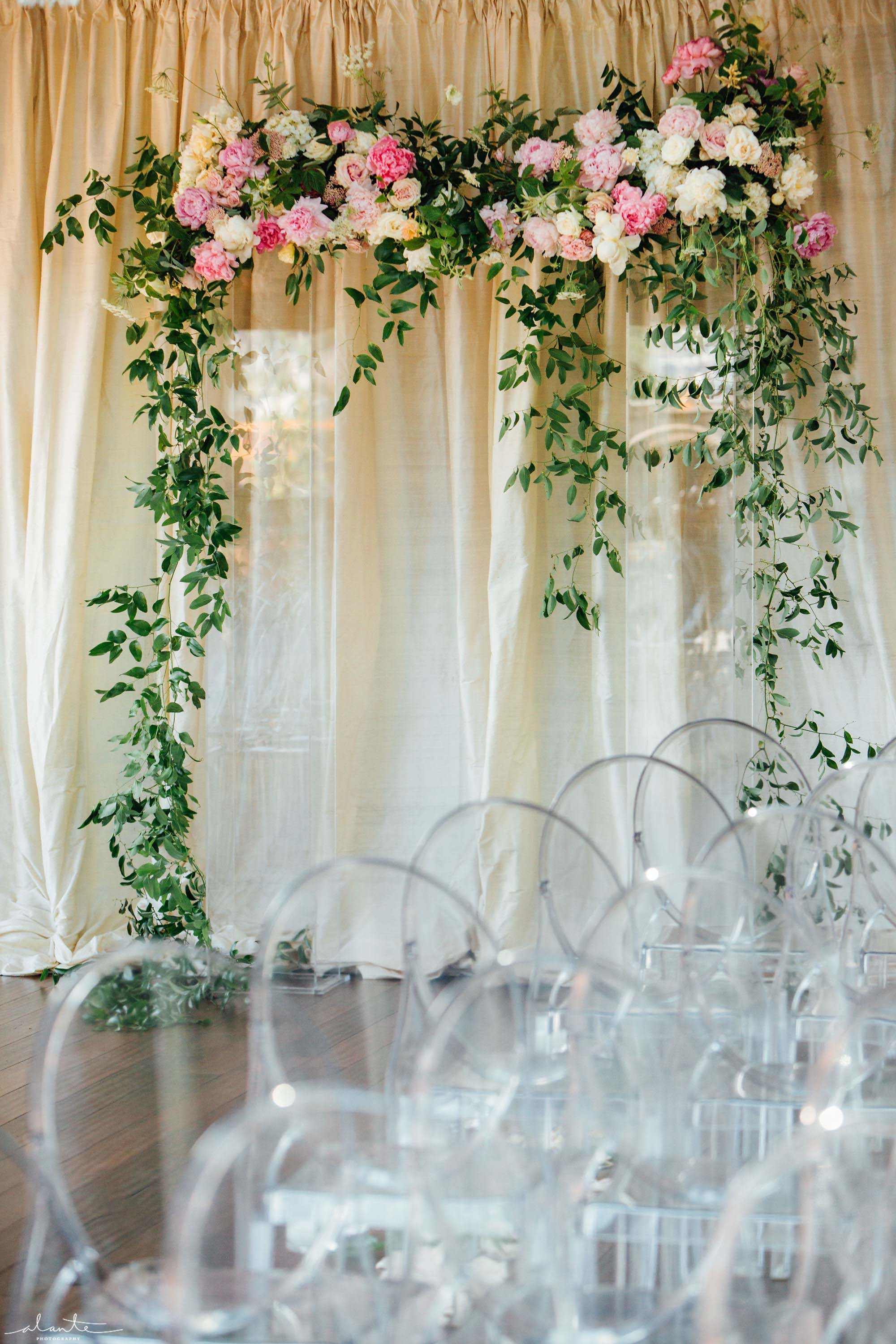 Wedding ceremony arbor of clear lucite pillars covered in greenery and blush flowers - Olympic Rooftop Pavilion wedding with pink peonies by Flora Nova Design Seattle