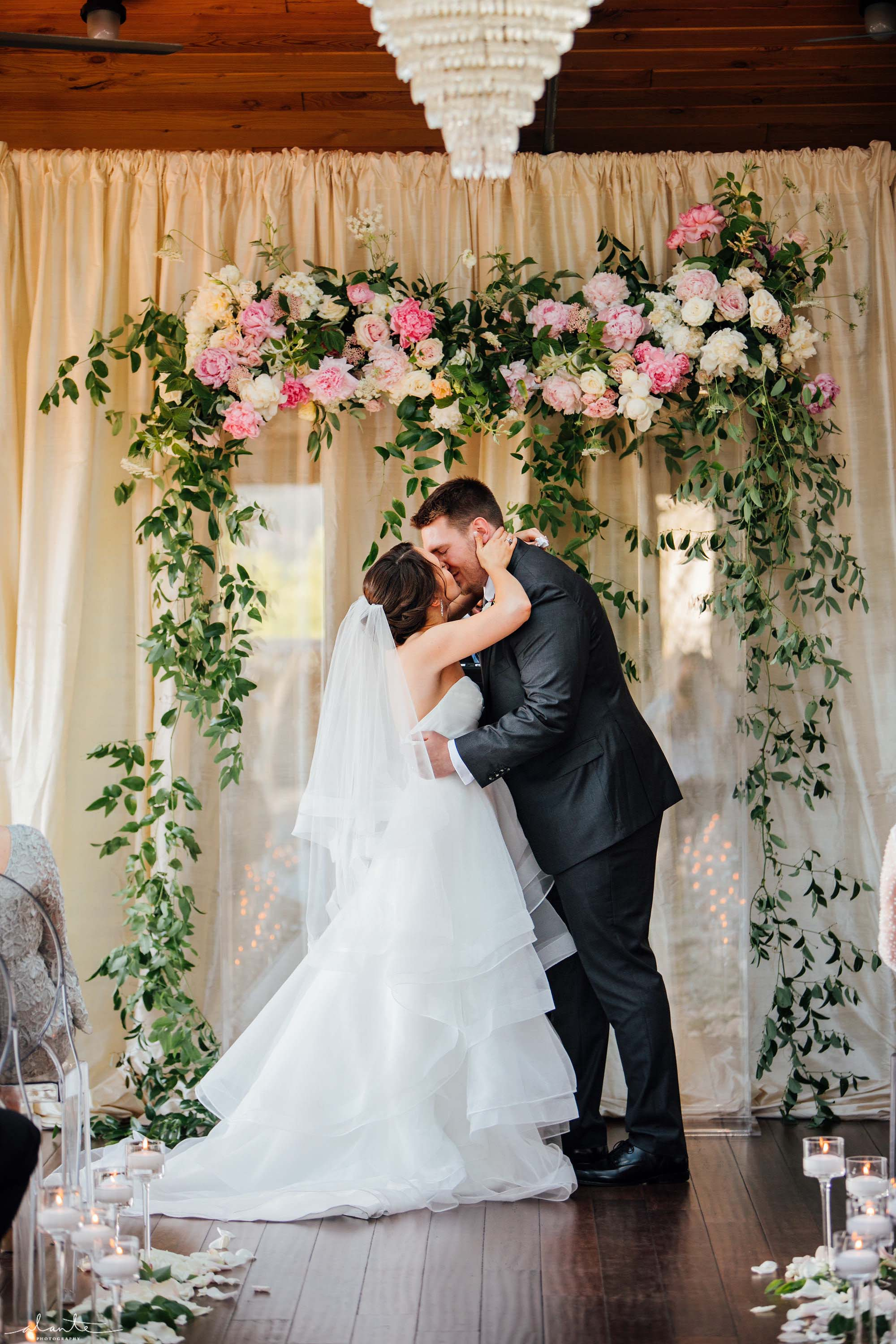 Bride and groom with greenery covered lucite wedding arch at Olympic Rooftop Pavilion - Olympic Rooftop Pavilion wedding with pink peonies by Flora Nova Design Seattle