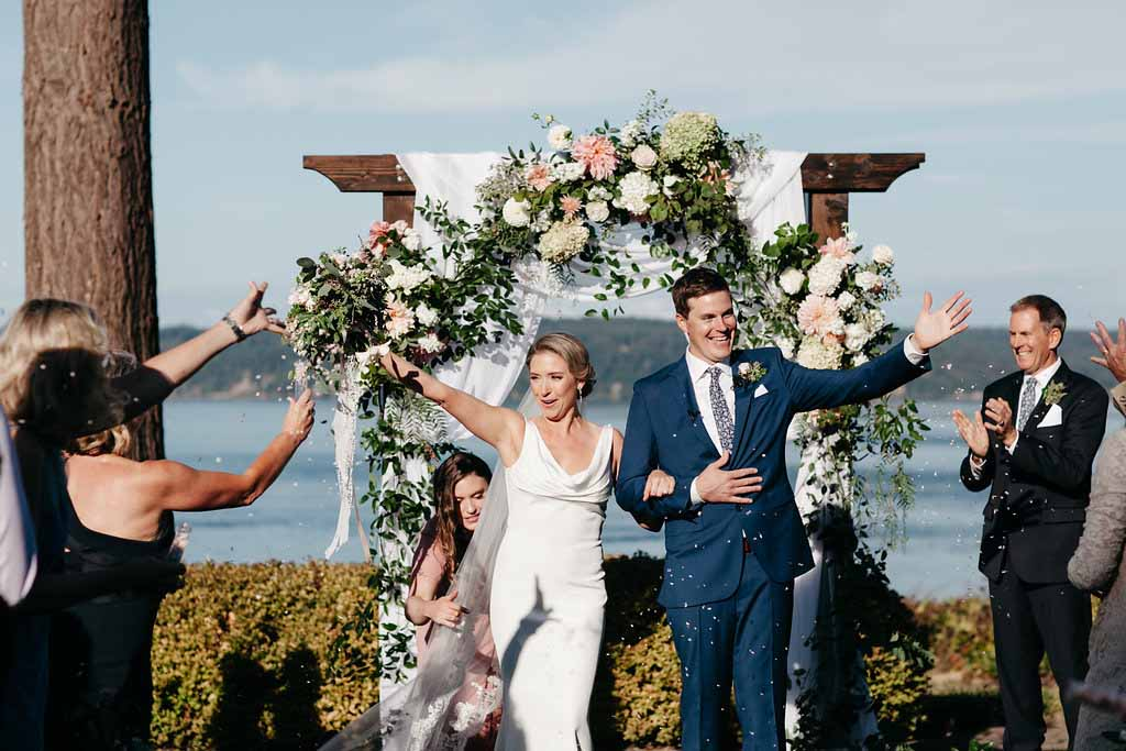 Bride and groom just married walking down aisle, with wedding arbor covered in greenery, Elegant Seattle Garden Wedding by Flora Nova Design Seattle