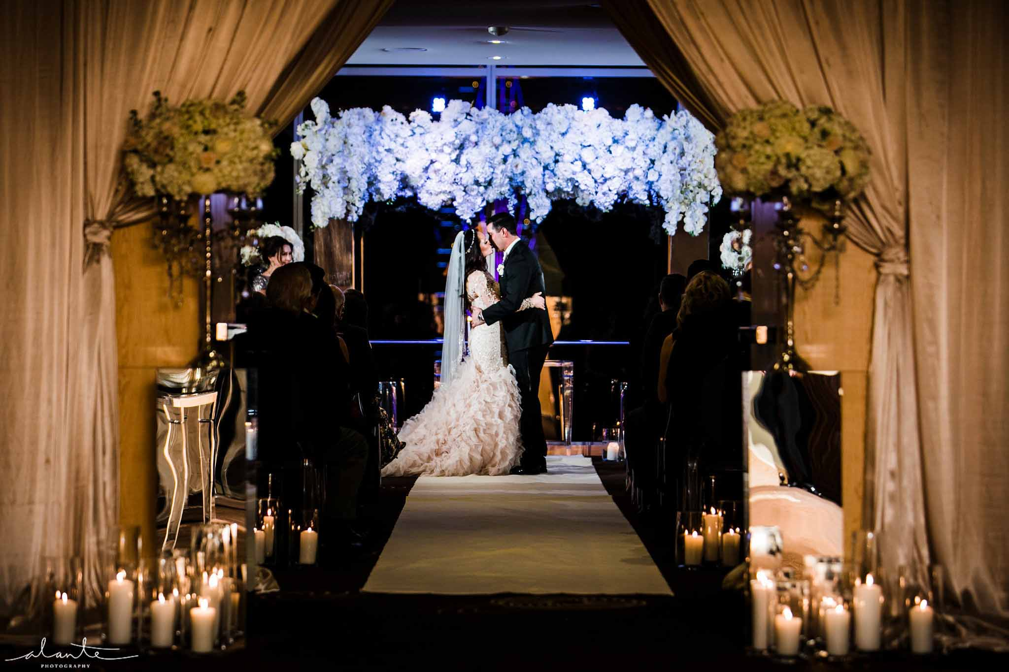 Bride and groom kissing at their winter evening wedding under arch of white orchids - Luxury Winter Wedding at the Four Seasons by Flora Nova Design Seattle