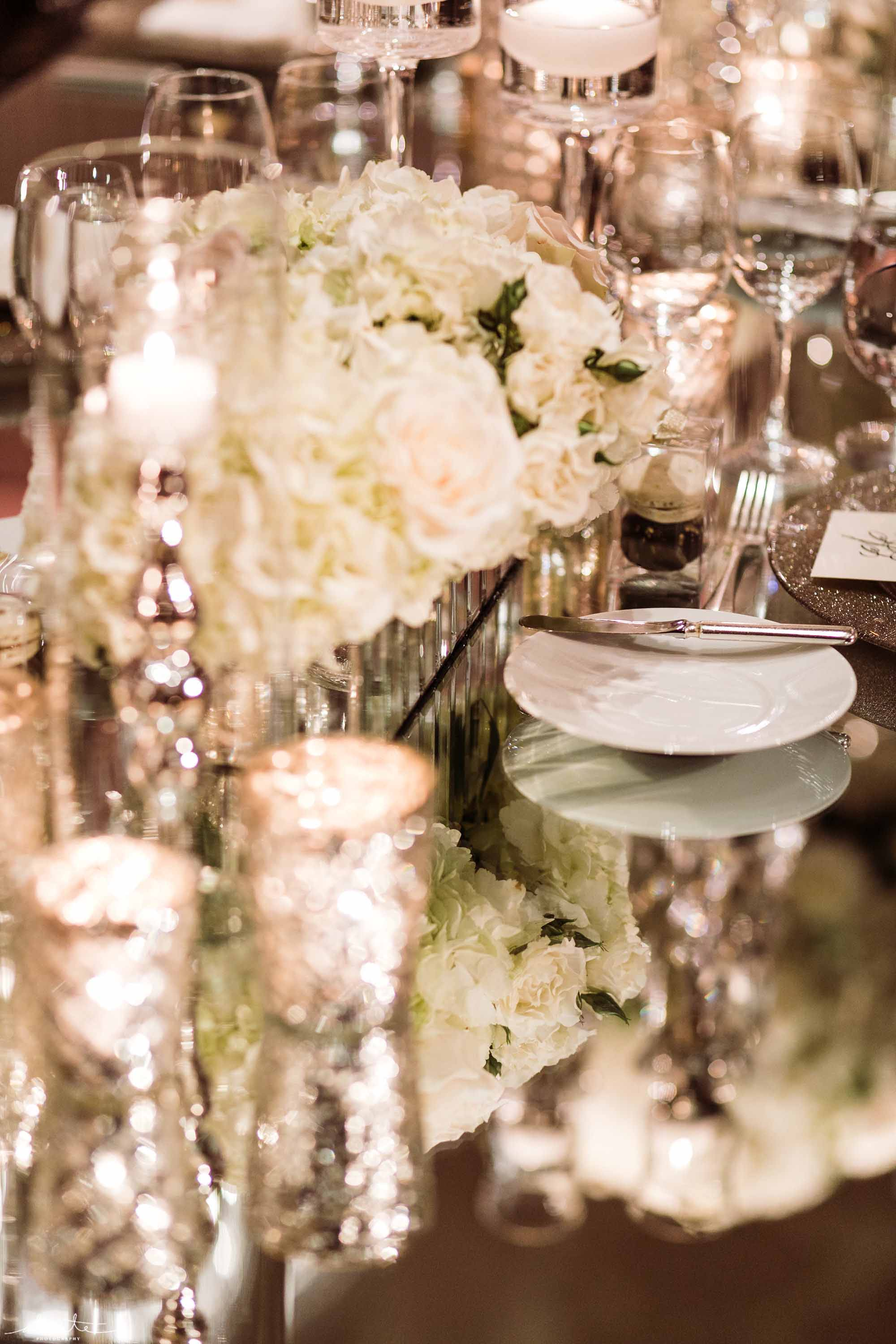 candles and white centerpieces in mirrored table - Luxury Winter Wedding at the Four Seasons by Flora Nova Design Seattle