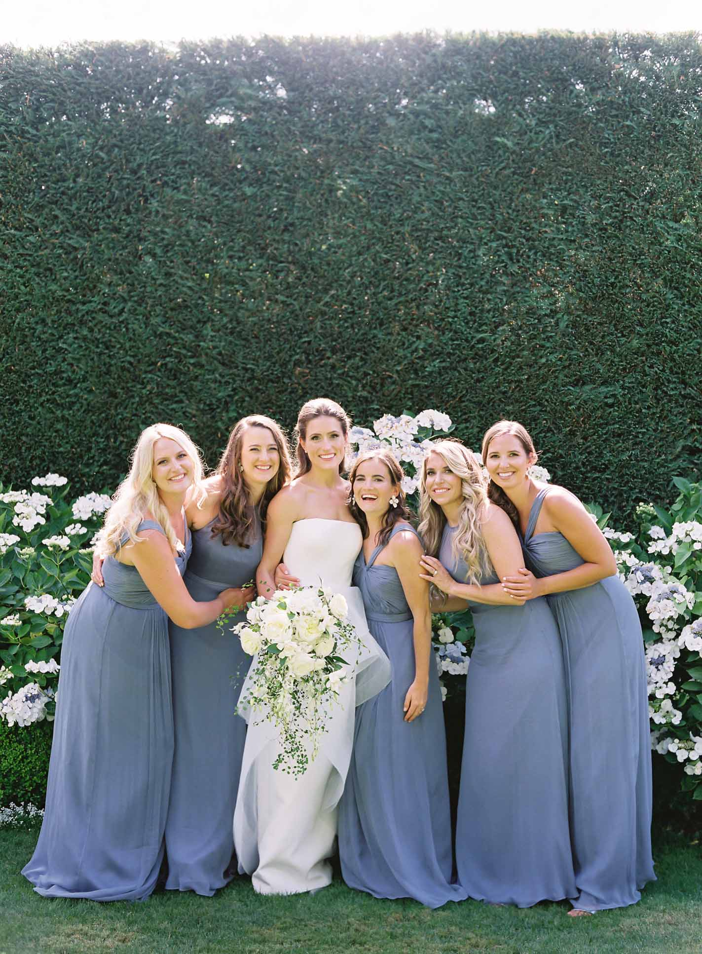 Bride with cascading bridal bouquet with bride's maids in blue dresses