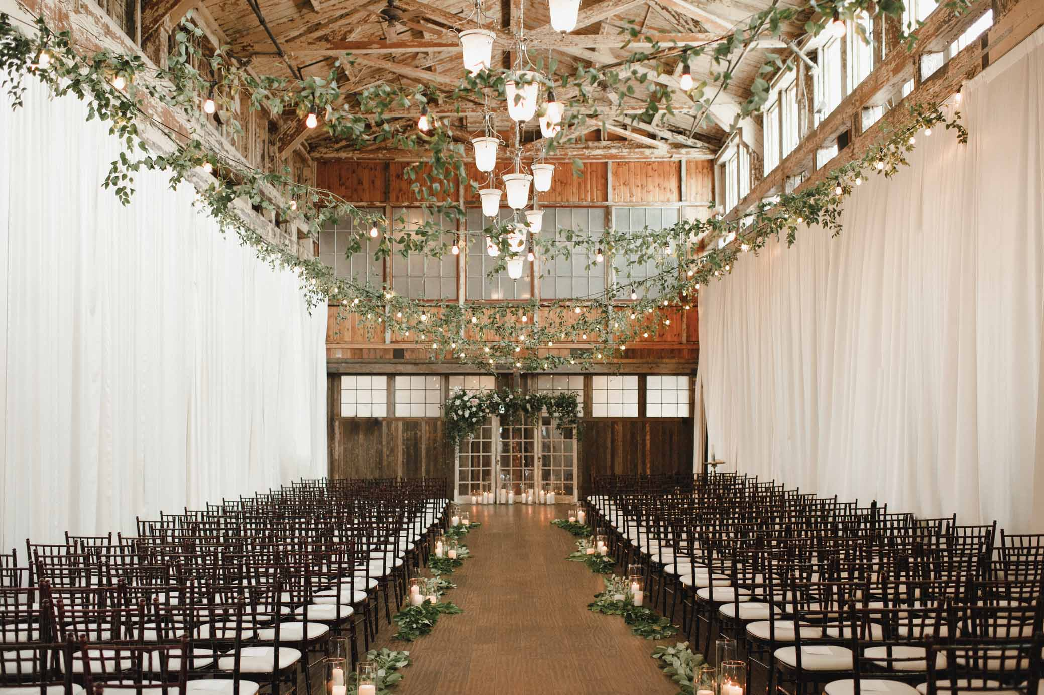 Sodo Park Seattle decorated for a wedding with ceiling greenery and a green wedding arch, candle lined aisle - designed by Flora Nova Design Seattle