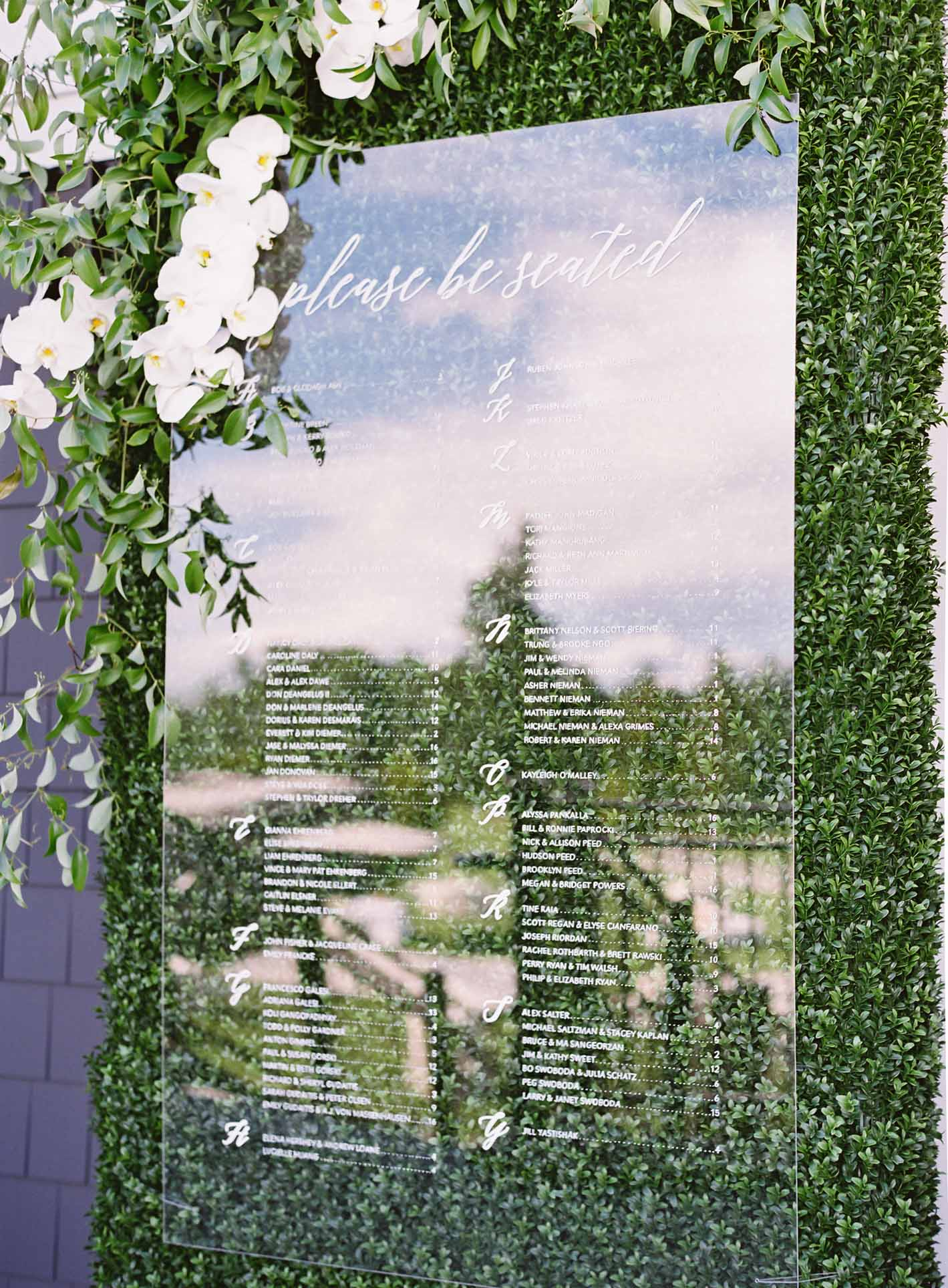 Clear lucite seating chart attached to boxwood greenery wall, adorned with white orchids