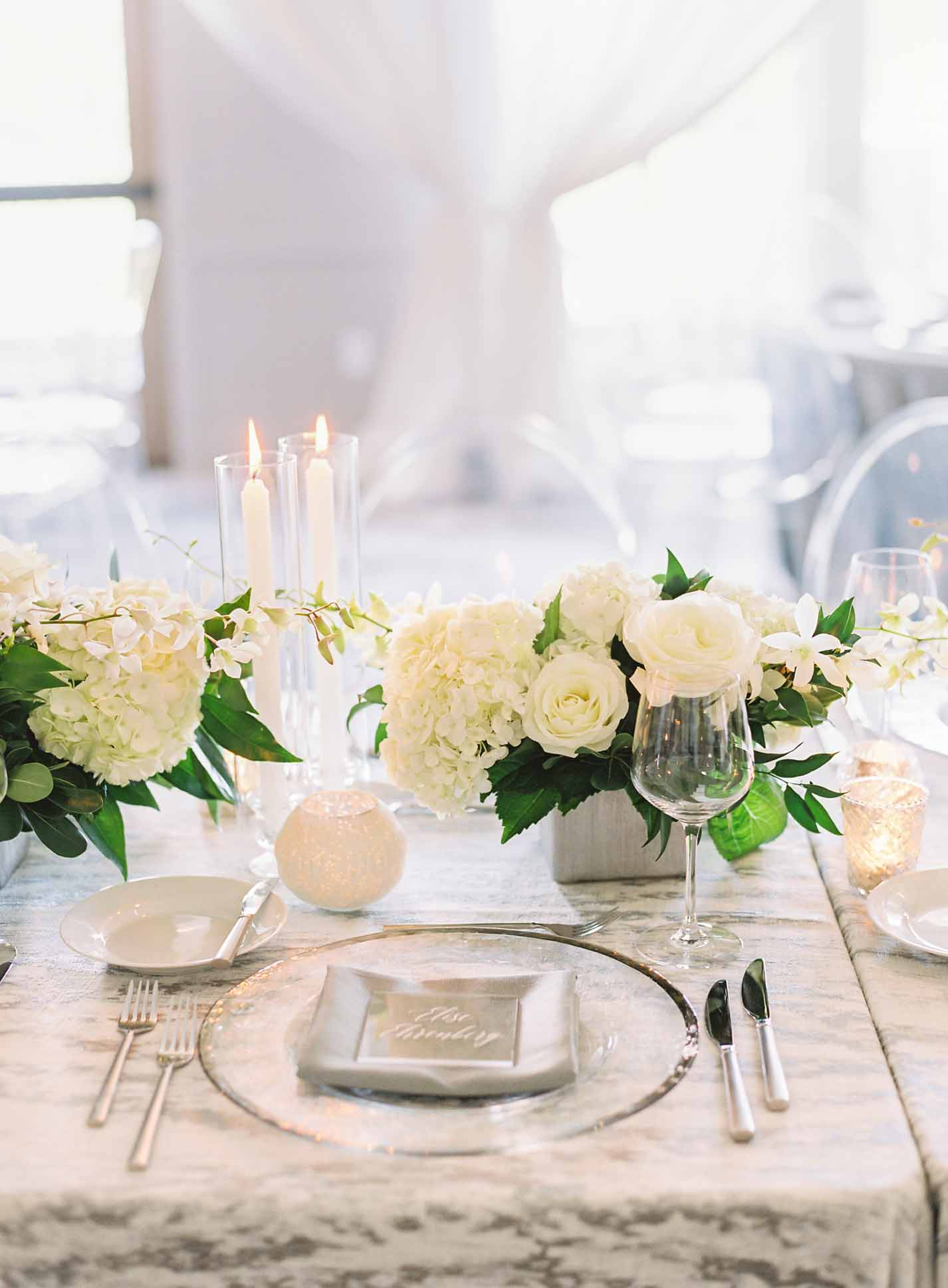 White centerpieces with greenery, in silver vases with taper candles, and silver rimmed charger plate