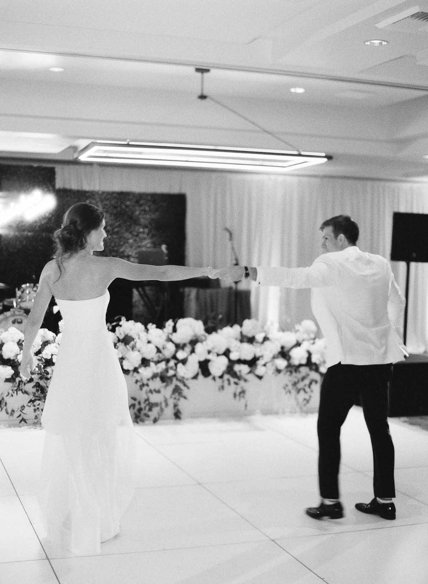 Wedding couple dancing in front of white hydrangea flower planters