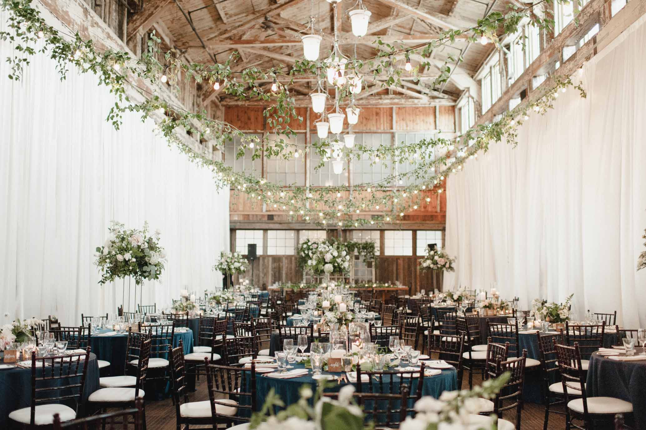 Wedding reception at Sodo Park Seattle with blue linens, greenery in ceiling, tall and low centerpieces - designed by Flora Nova Design Seattle