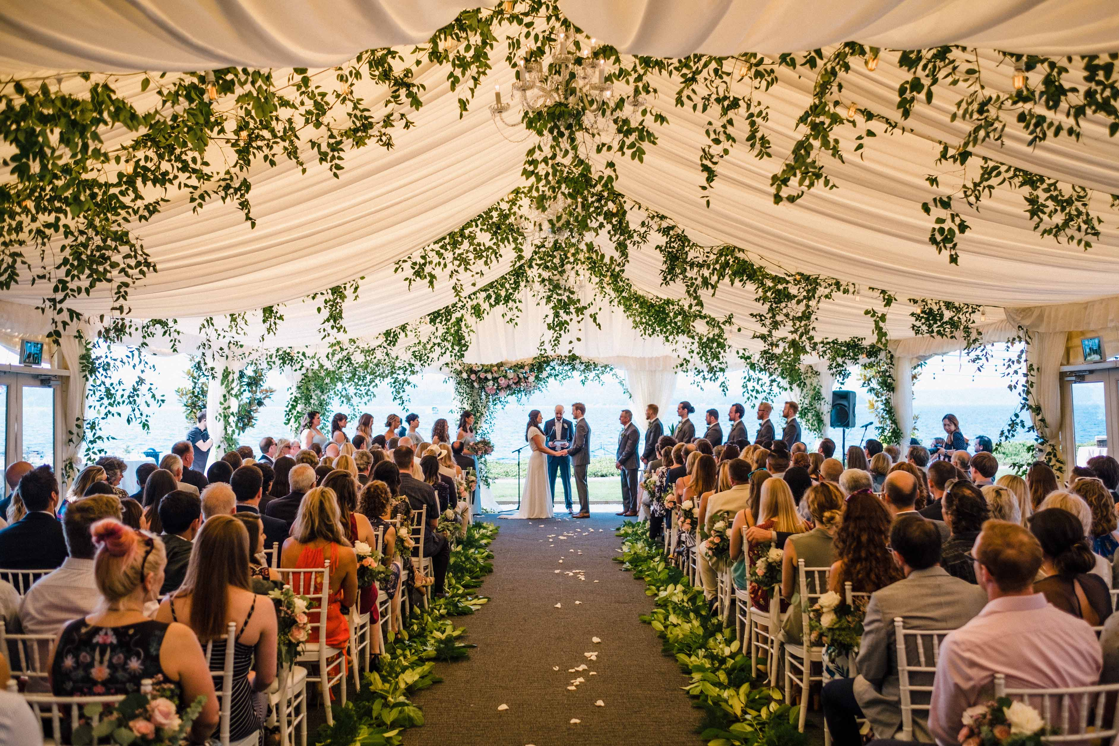 Wedding ceremony with lots of greenery in the tent ceiling at a Woodmark Hotel wedding, Flora Nova Design Seattle