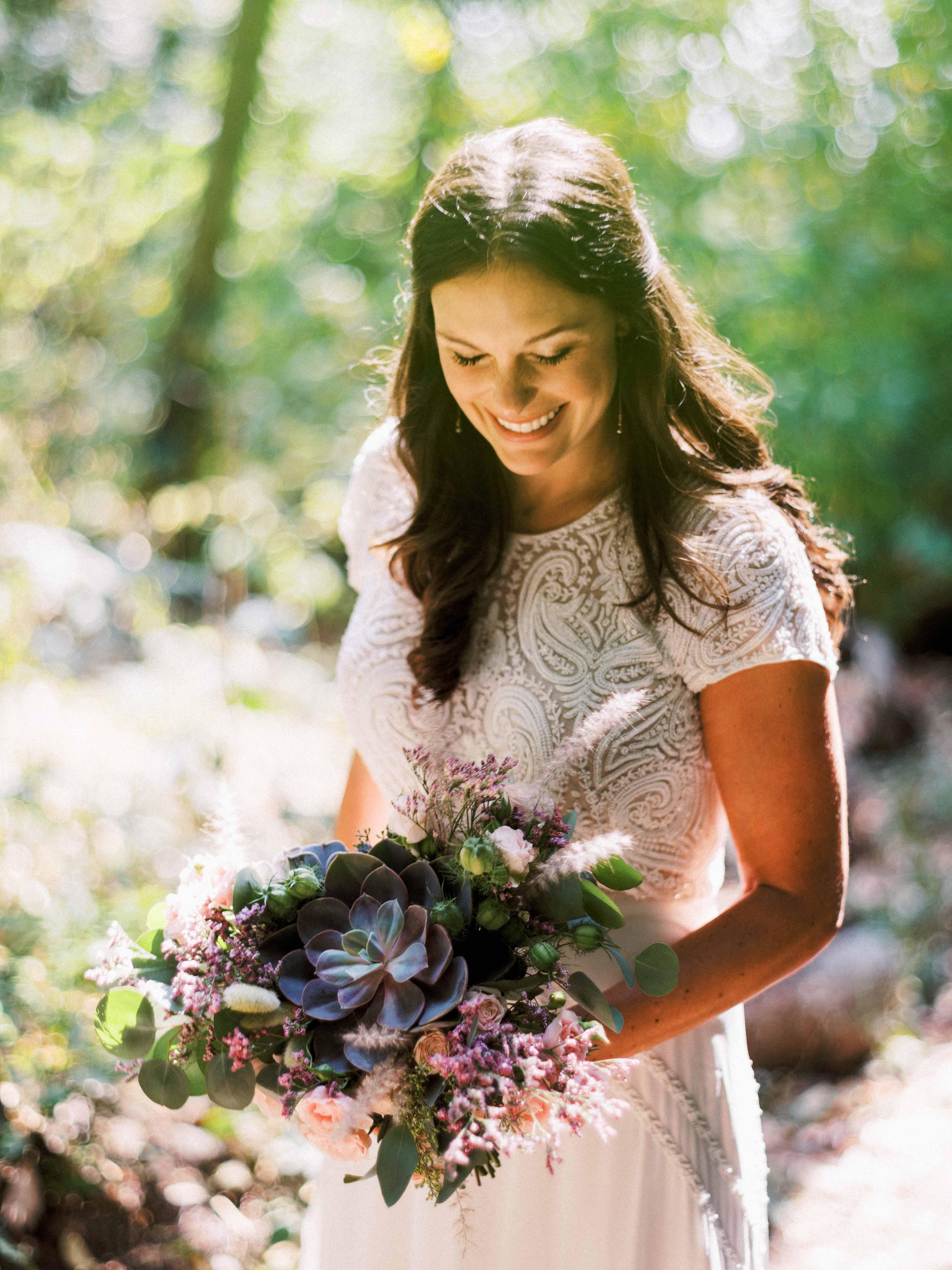 Bride holding wedding bouquet of succulents designed b Flora Nova Design