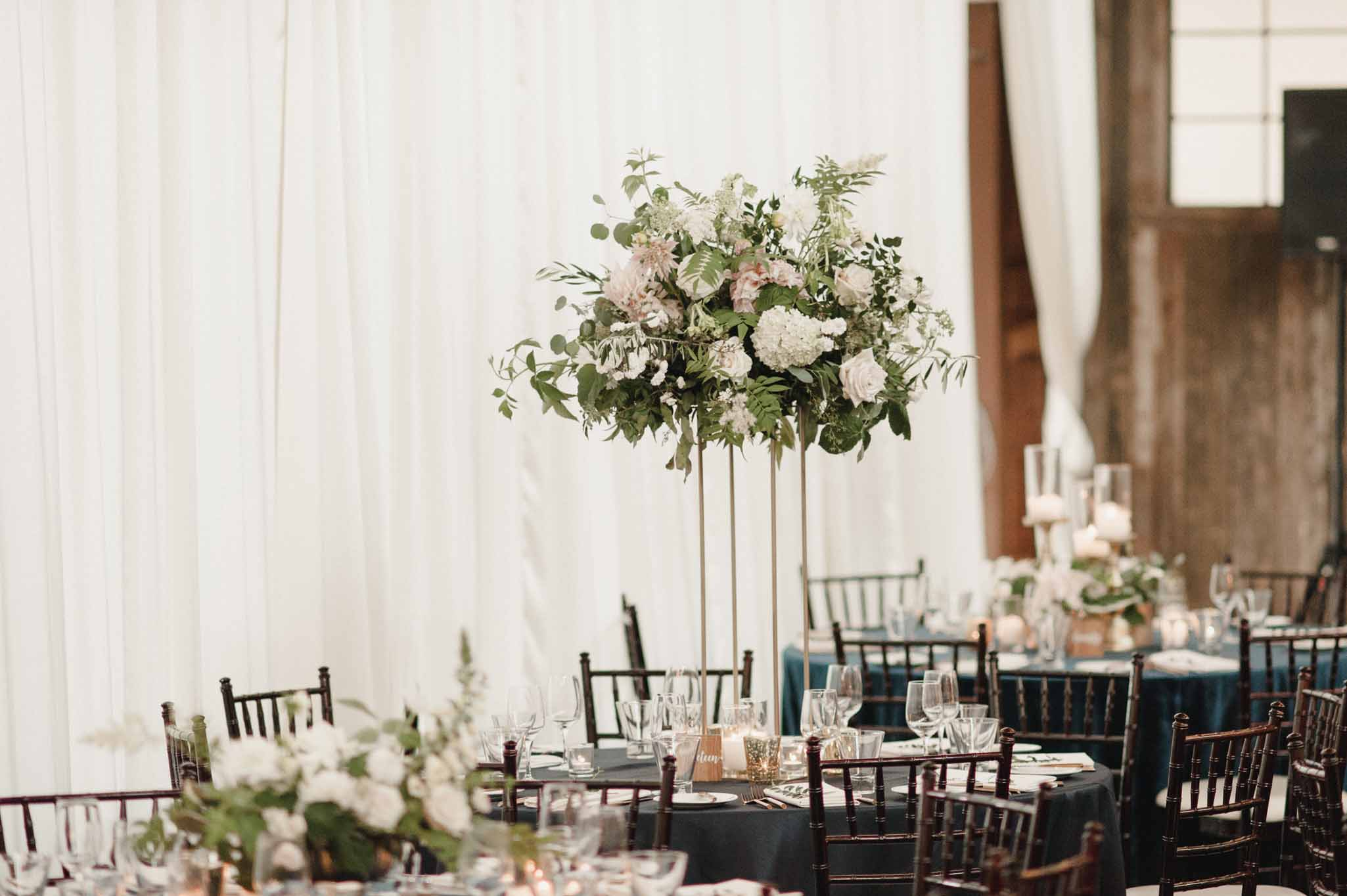Tall centerpiece of white hydrangea, cafe au lait dahlias, roses, and lots of greenery, on gold harlow stand, designed by wedding designer Flora Nova Design in Seattle