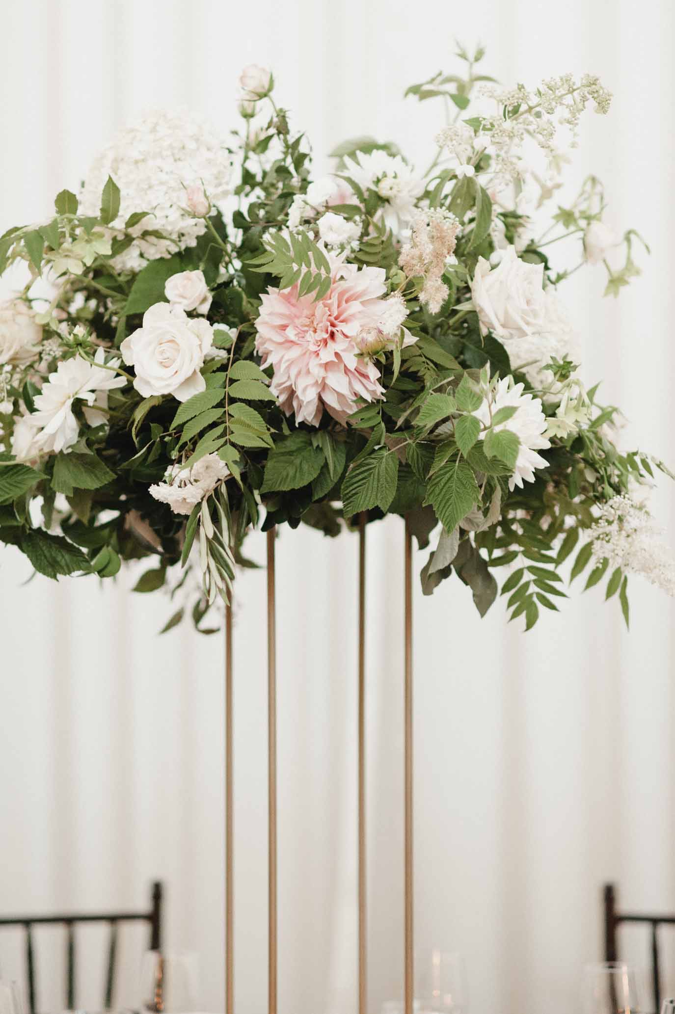 Floral centerpiece with lots of greenery, peach dahlias, white stock, and cream roses - by design company Flora Nova Design in Seattle