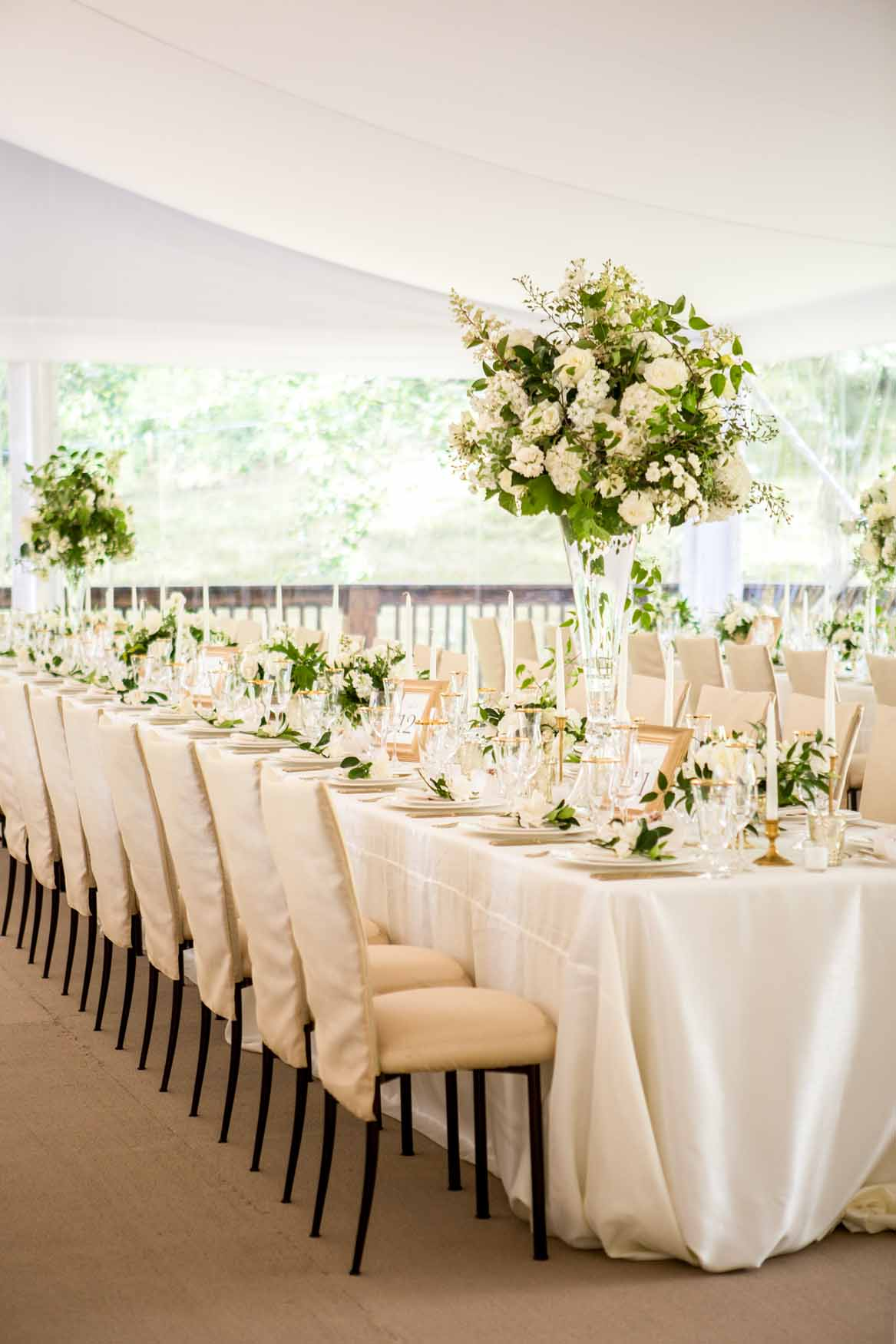 A long table filles with tall and low centerpieces - Elegant Summer Private Estate Wedding. Flora Nova Design Seattle