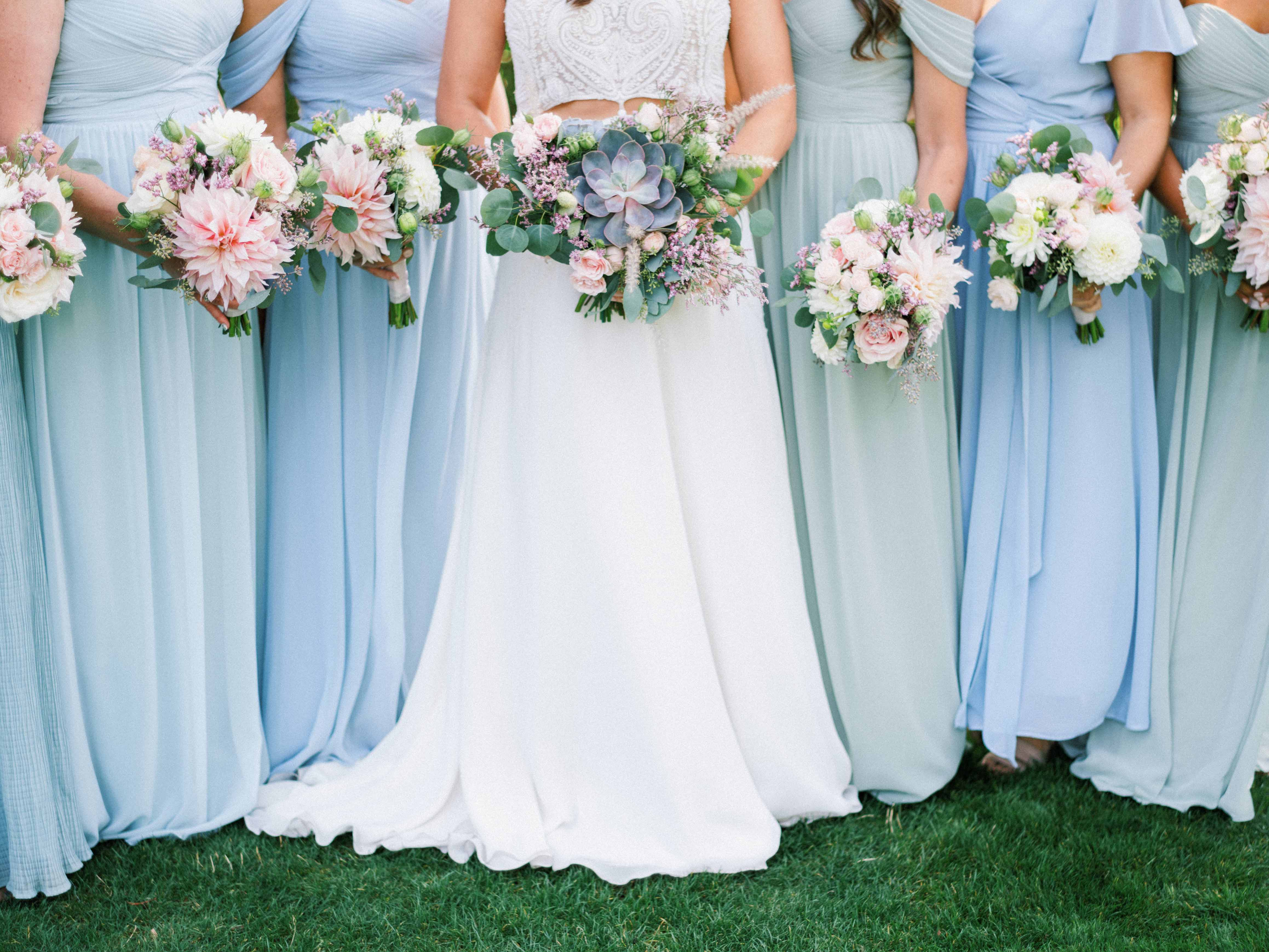 a bride with her brides maids holding bouquets by Flora Nova Design
