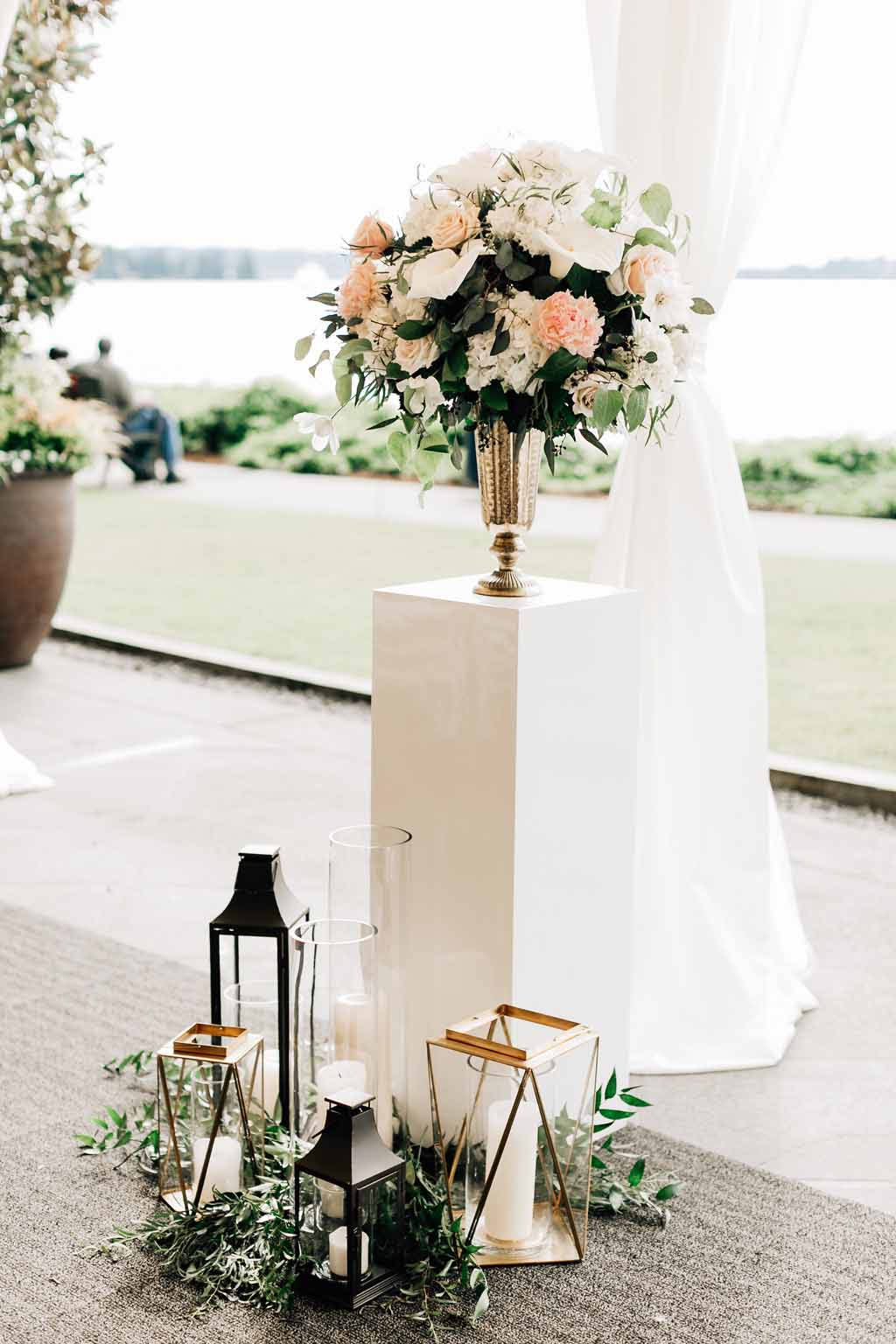 Wedding ceremony flowers  in gold urn, on top of white pedestal, with lanterns at base - Lake Washington Wedding