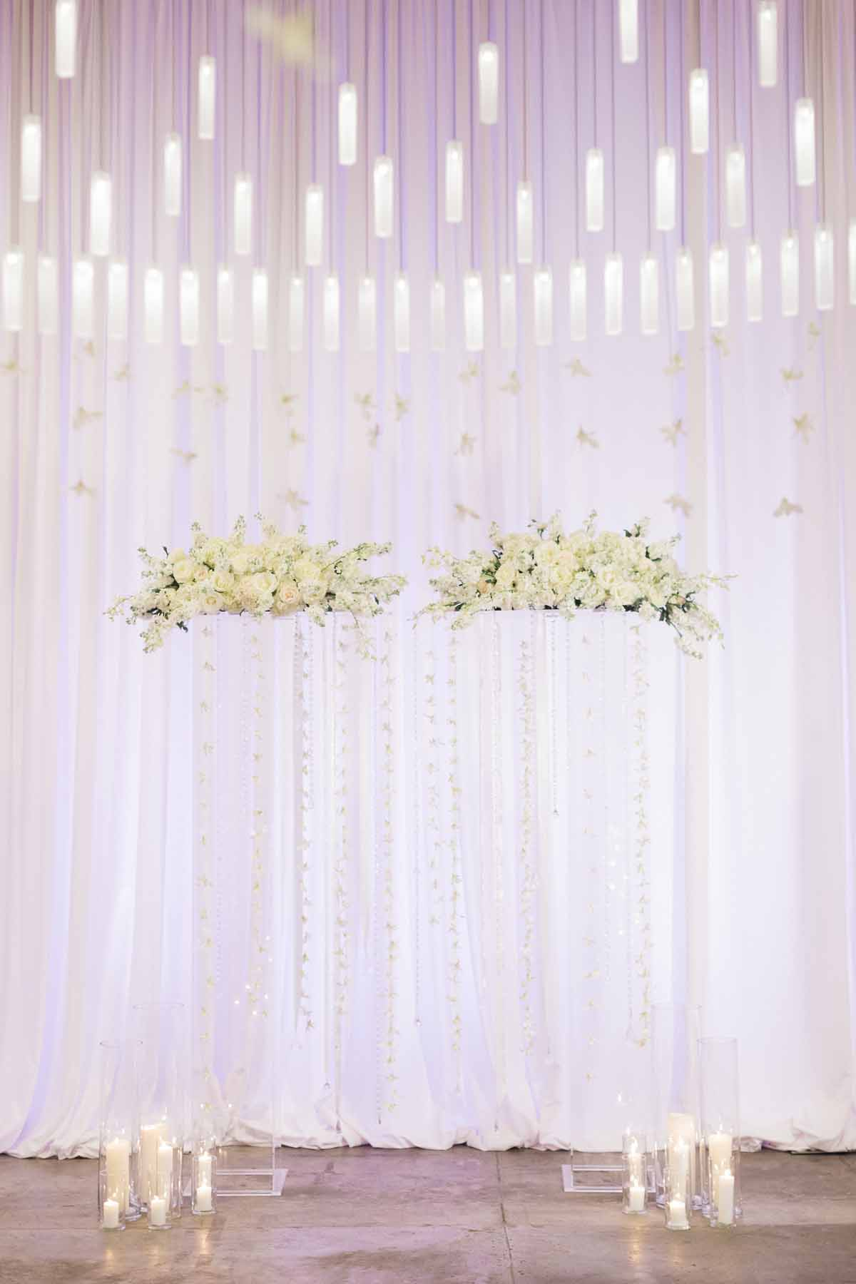 Ethereal wedding arch with clear lucite pillars, crystal strands, white flowers, and white draping - Canvas Event Space Wedding by Flora Nova Design