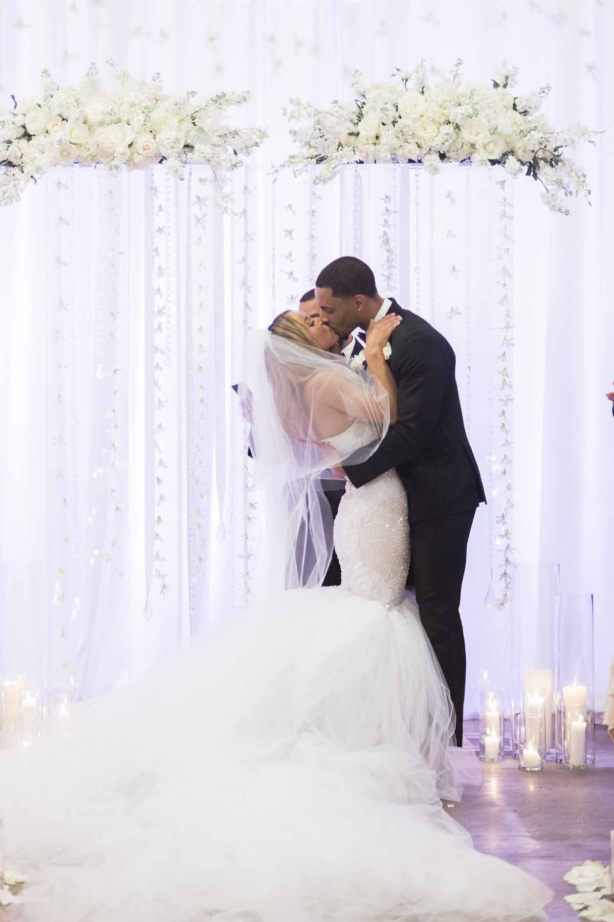 Bride and groom kissing in front of modern wedding arch in all white with clear lucite pillars