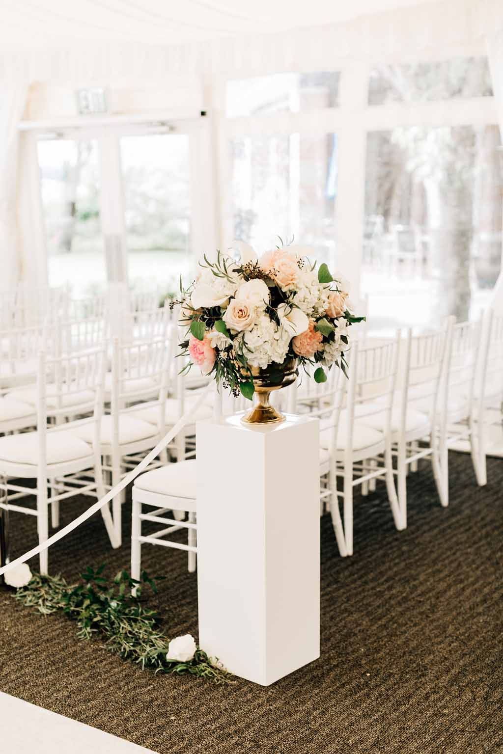 Aisle entry arrangement of spring flowers in gold compote vase propped onto white pedestal