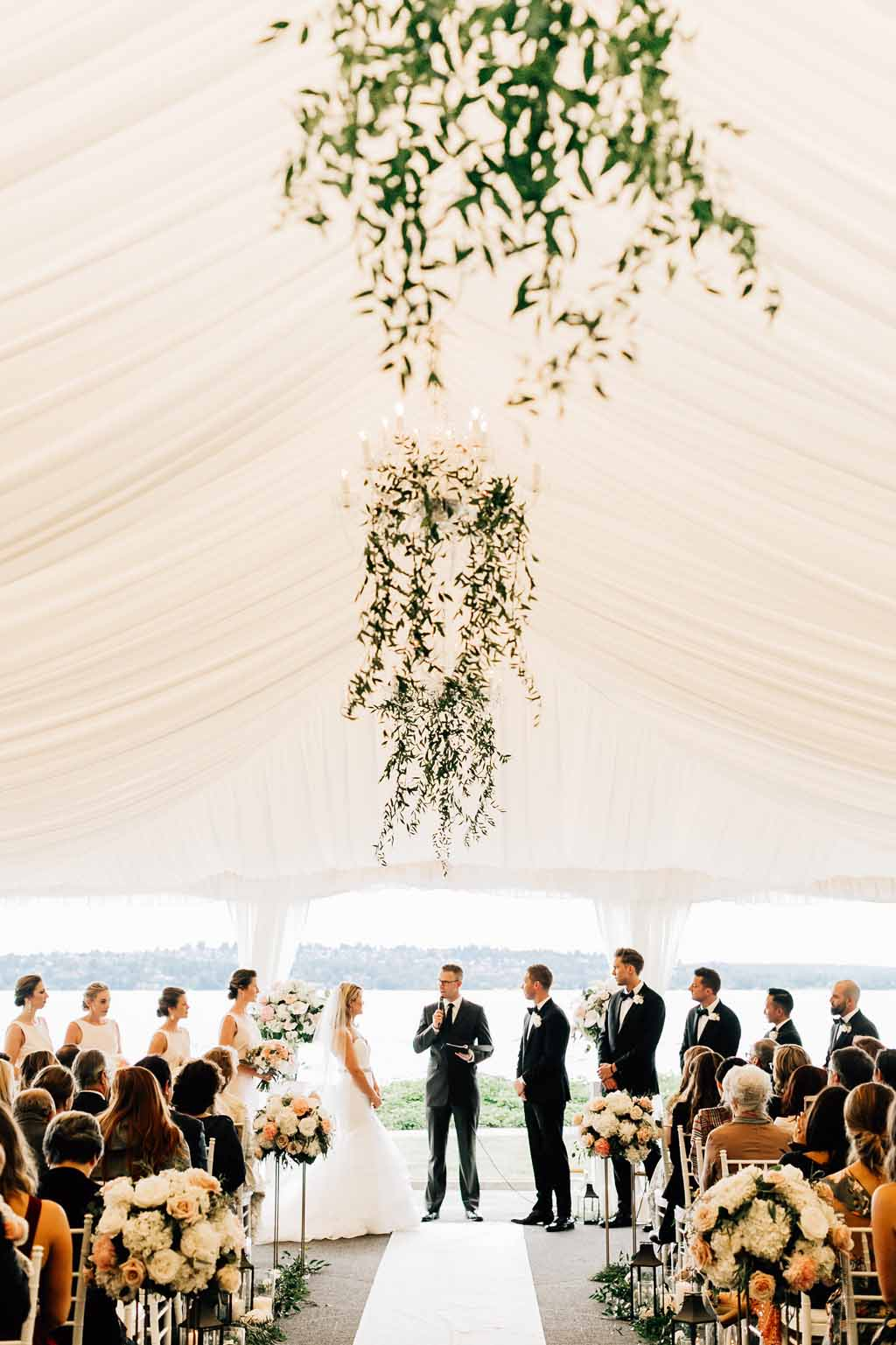 Wedding ceremony in tent at Lake Washington with greenery trailing from chandeliers