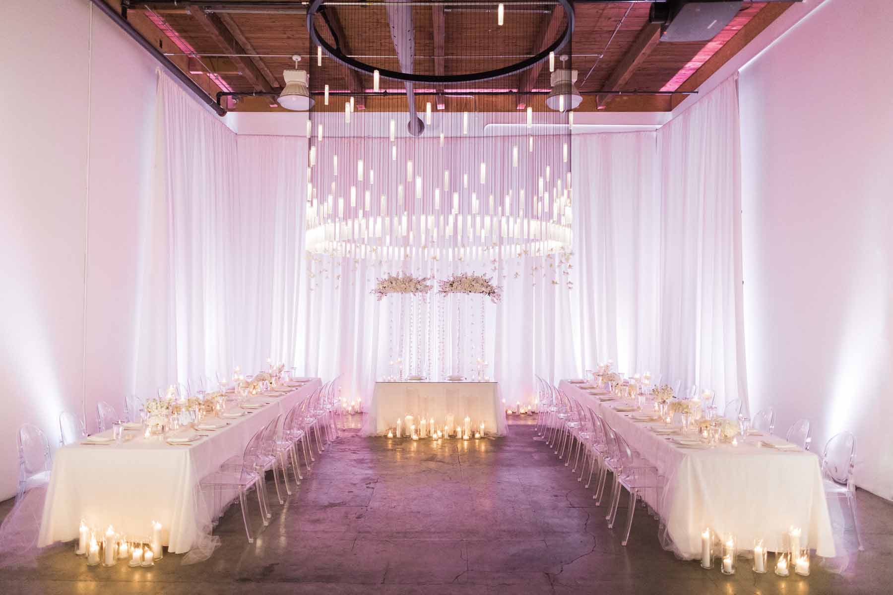 all white, modern wedding reception with ghost chairs and white draping