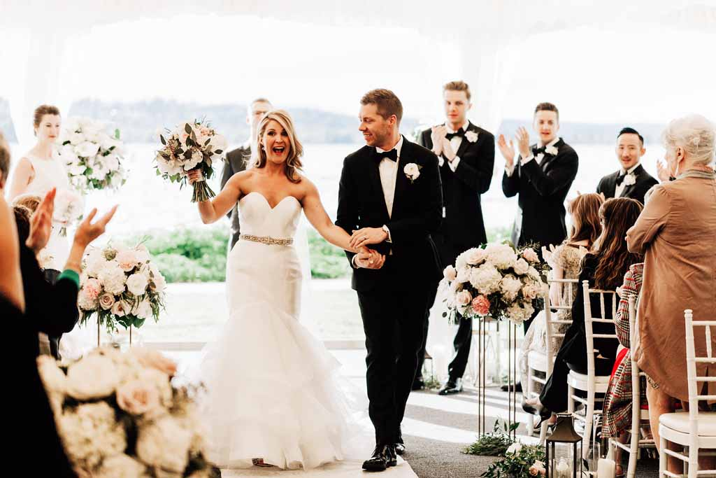 Happy wedding couple, just married, walking down flower lined wedding aisle - by Flora Nova Design