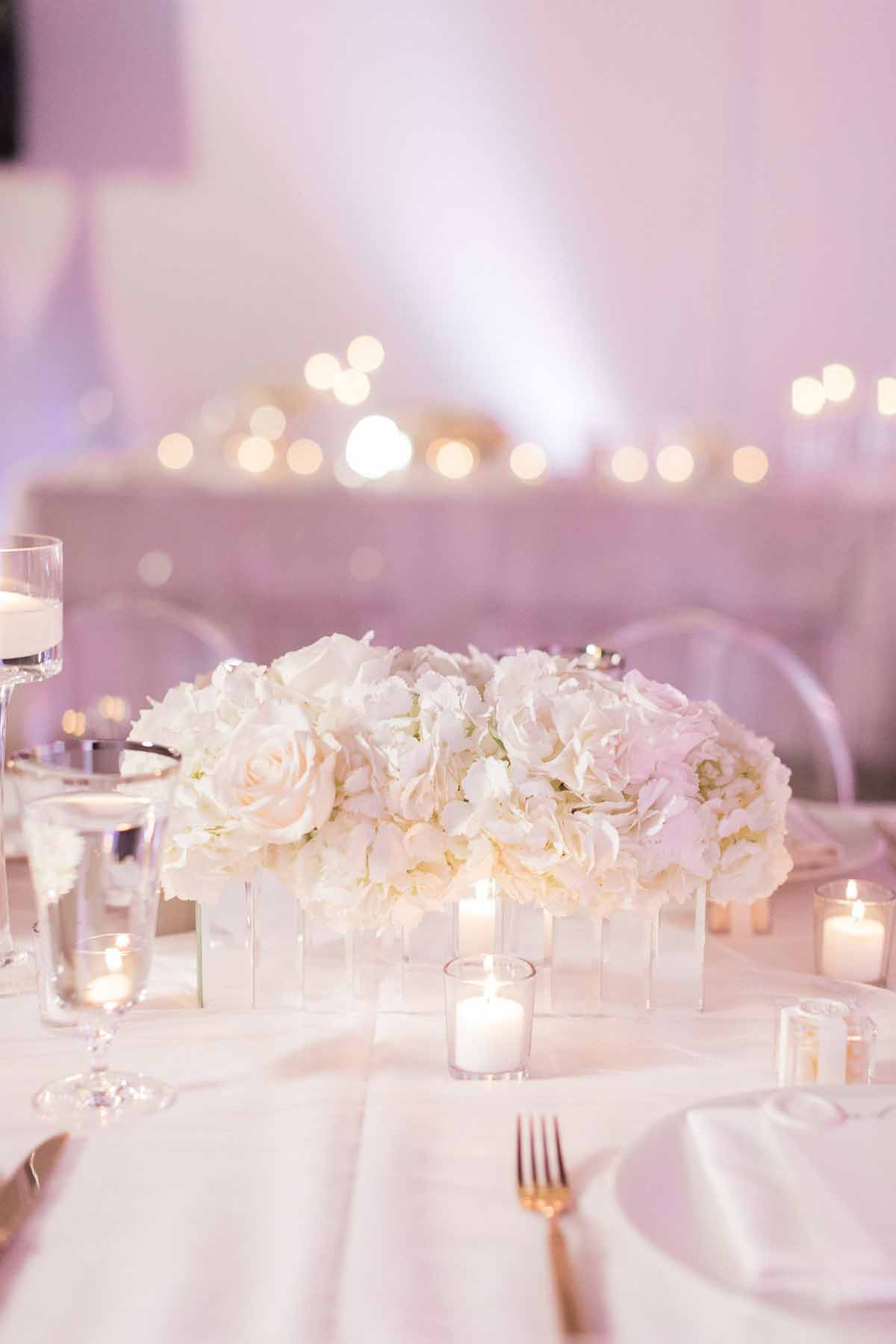 Centerpiece of white hydrangea and white roses and votive candles at Canvas Event Space wedding