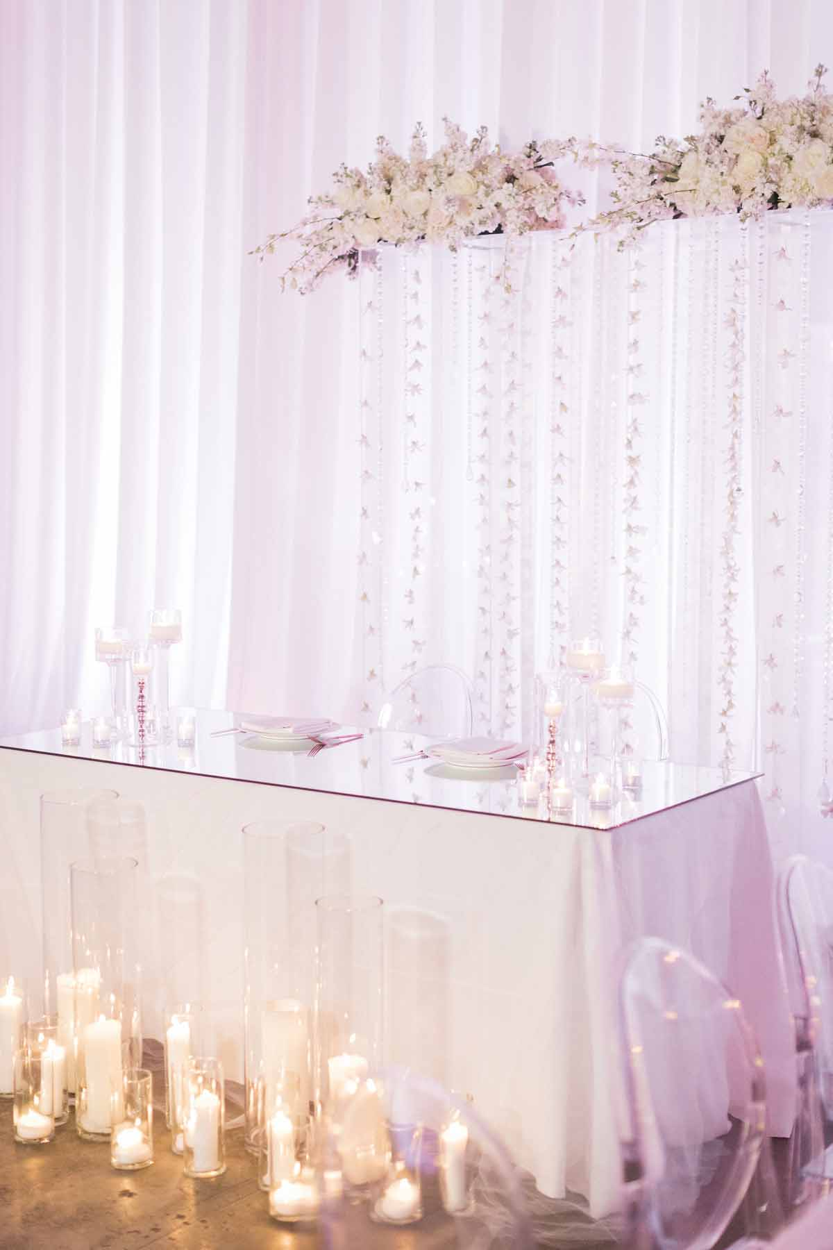 All white head table with white wedding floral arch and hurricane candles and clear lucite chairs - Canvas Event Space wedding
