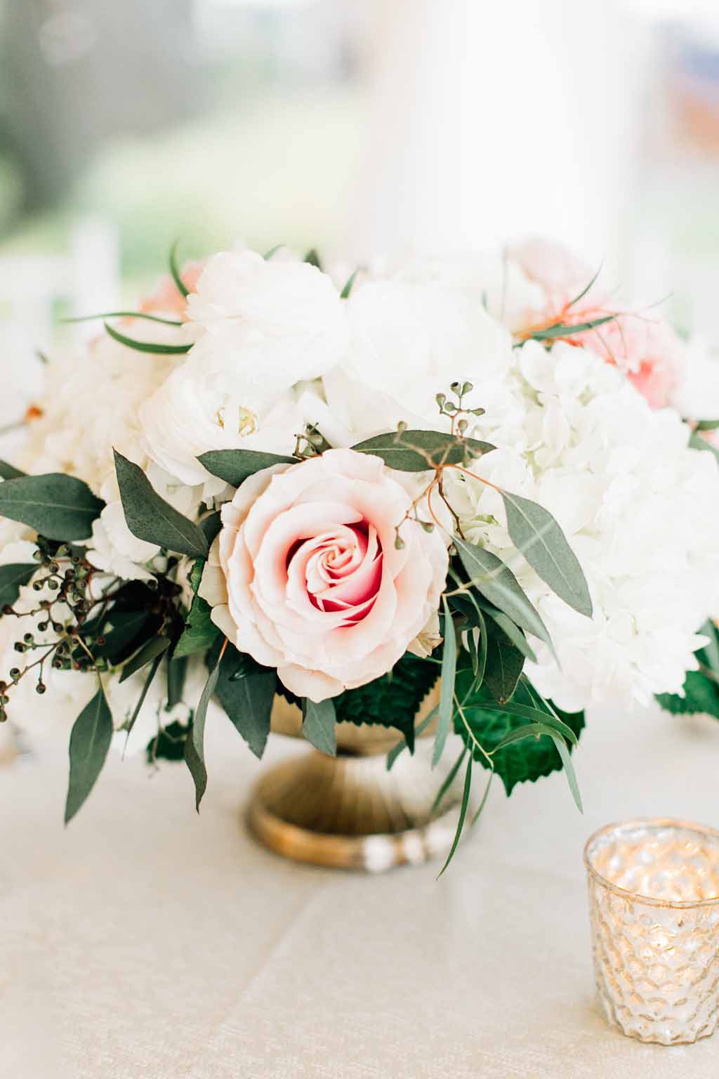 Centerpiece of peach roses, white peonies, white hydrangea, and eucalyptus greenery