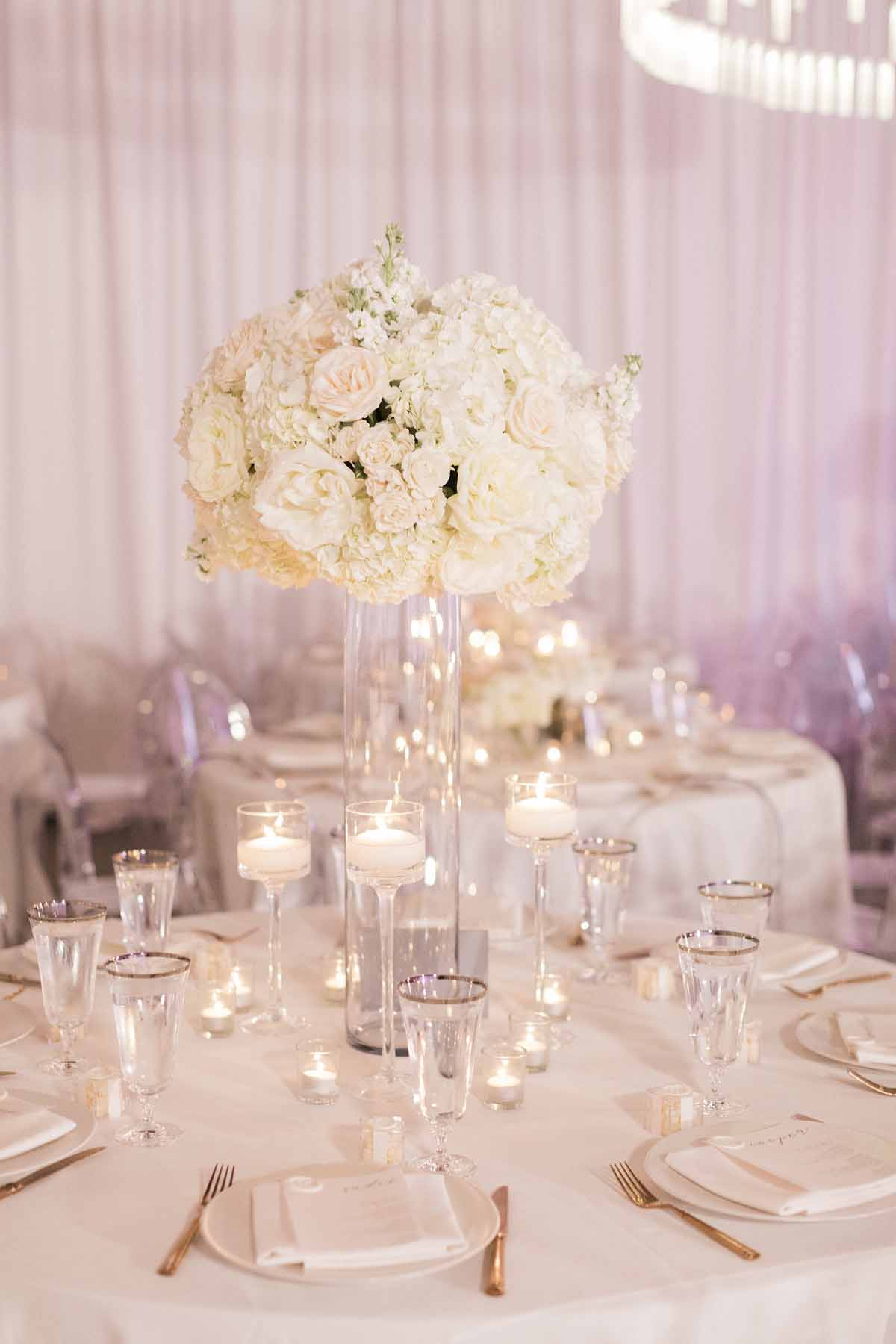 Tall, white centerpiece of white roses and white hydrangea
