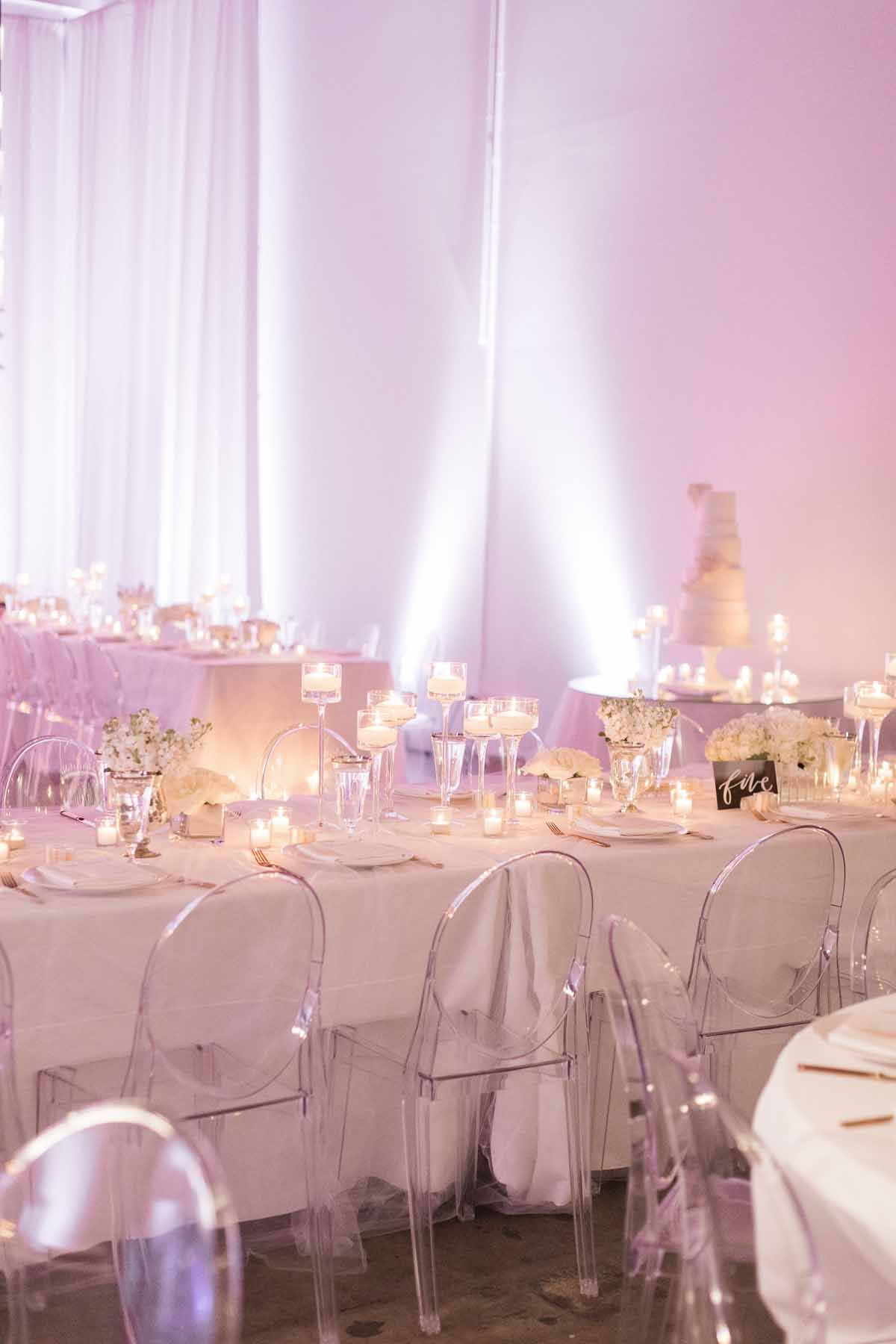 Modern white wedding at Canvas Event Space in Seattle: floating candles and white centerpieces, with white draping, white linens, clear lucite chairs - by Flora Nova Design