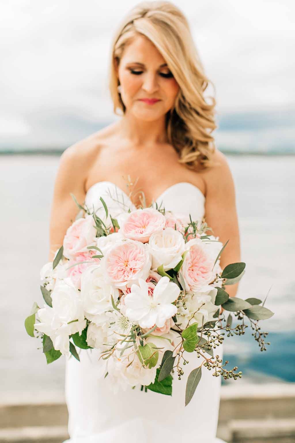 Bride holding her bouquet of peach Juliet garden roses and white peonies, with trailing eucalyptus greenery