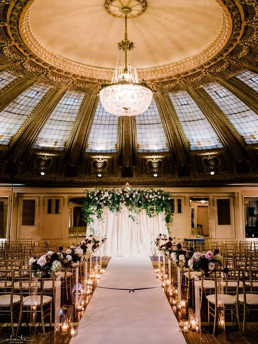 Draped ceremony arch with lush greenery and roses in the Dome Room at the Arctic Club Seattle
