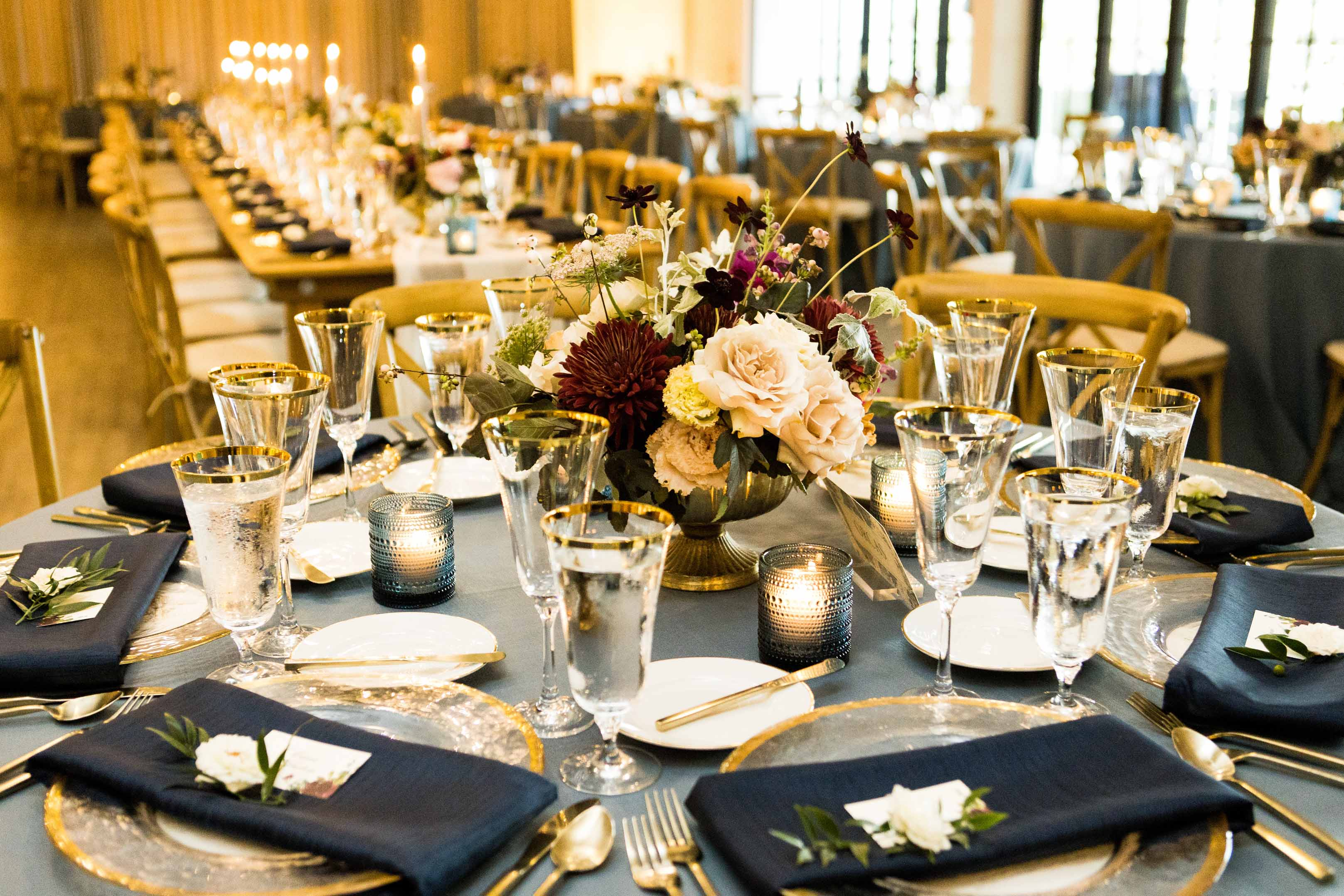Floral centerpiece of fall flowers on French blue linen, long tables with Vineyard chairs