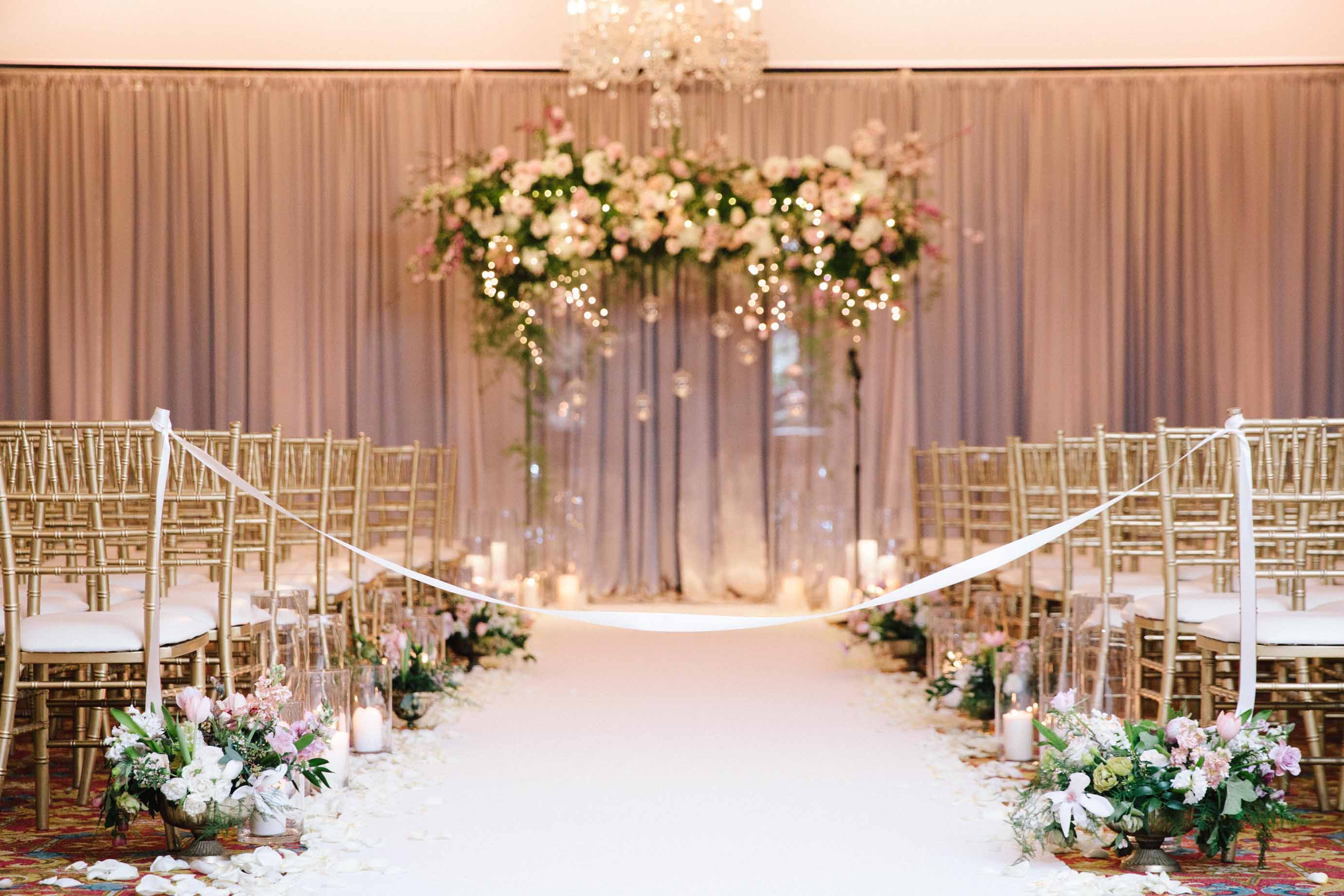 Large spring garden floral arch for wedding ceremony in front of white aisle lined with candles and flowers
