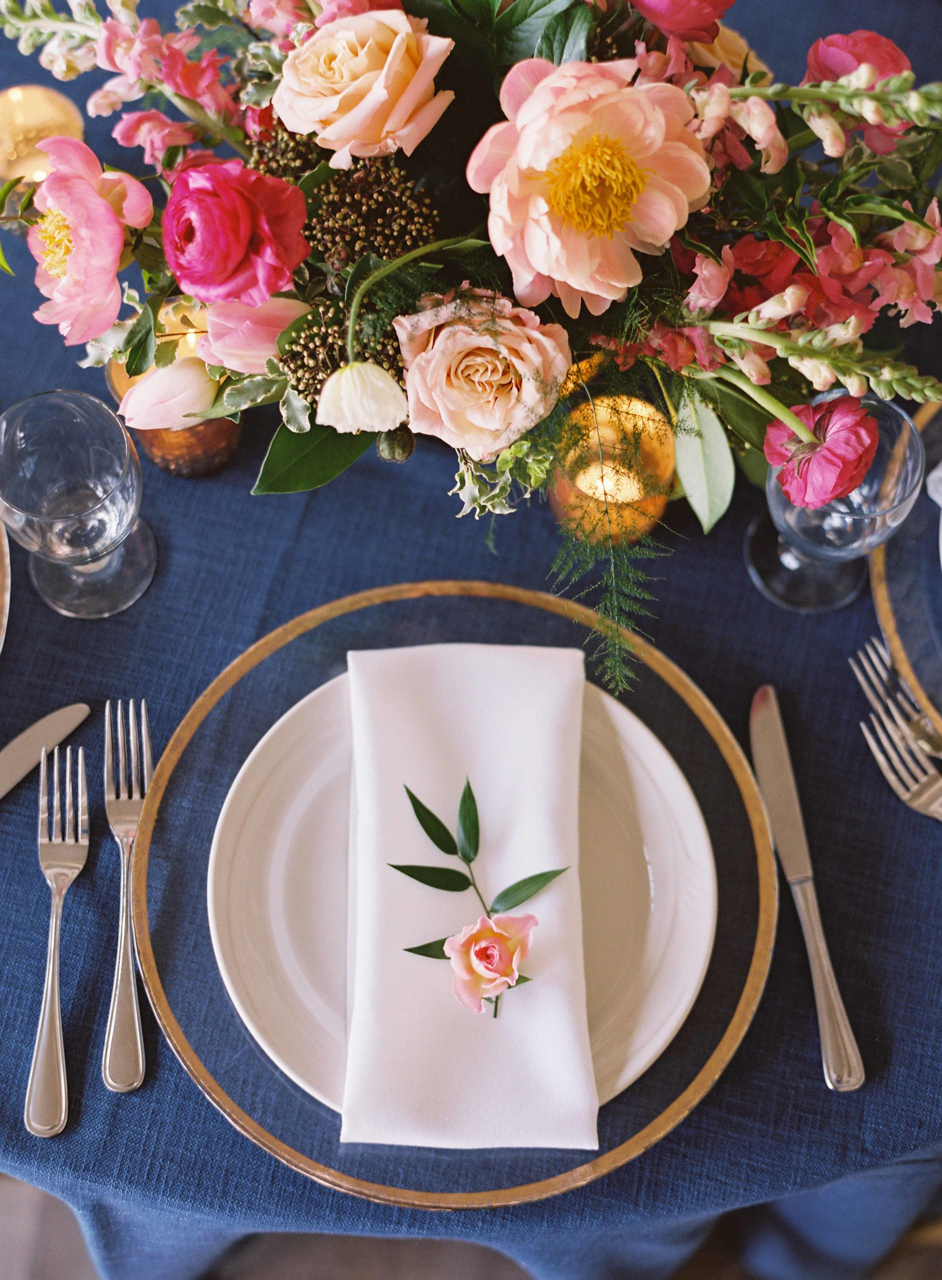 Hot pink and peach centerpiece next to gold charger plates, white napkin, and peach rose napkin flower - Seattle Wedding Flowers by Flora Nova Design; Hot pink and peach wedding at Roche Harbor Resort