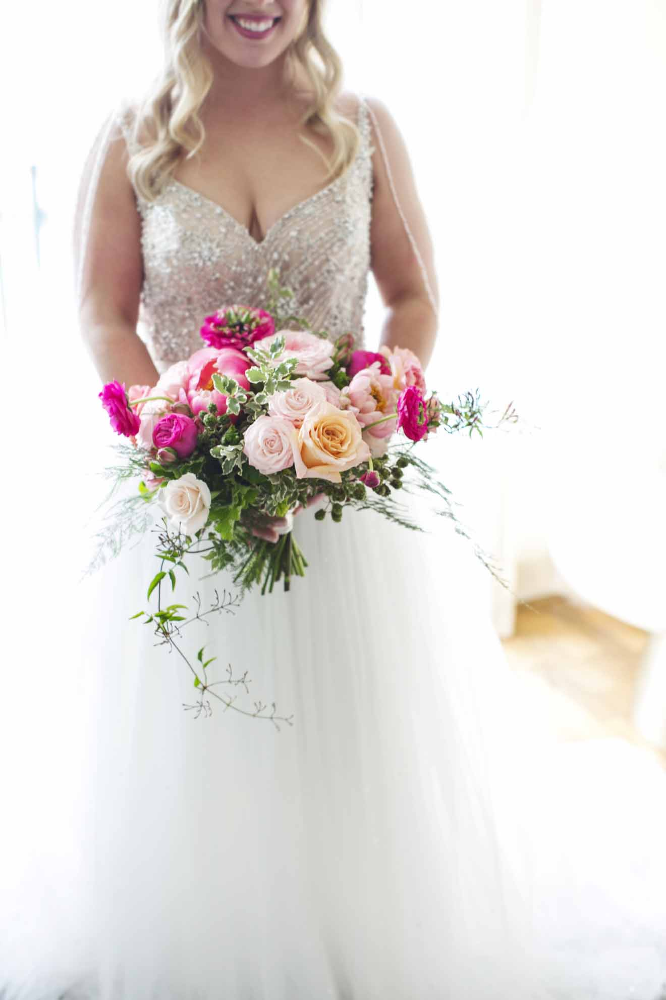 Hot pink and peach wedding bouquet with trailing greenery held by bride in white wedding dress - Seattle Wedding Flowers by Flora Nova Design; Hot pink and peach wedding at Roche Harbor Resort